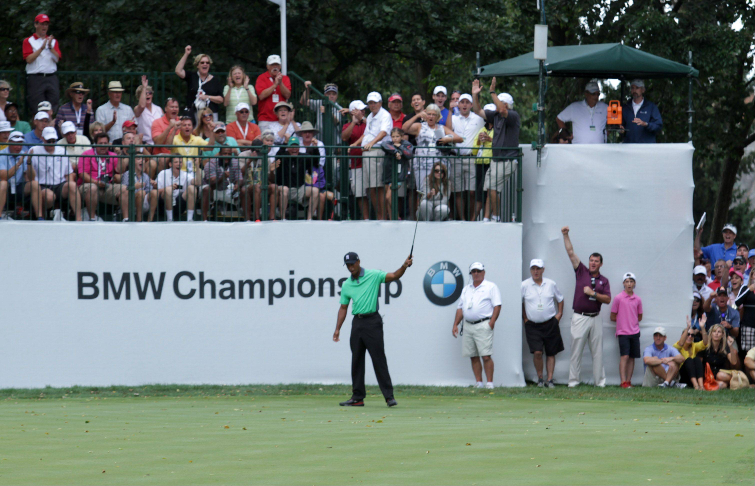 Fans cheer as Tiger Woods sinks a putt on the 9th.