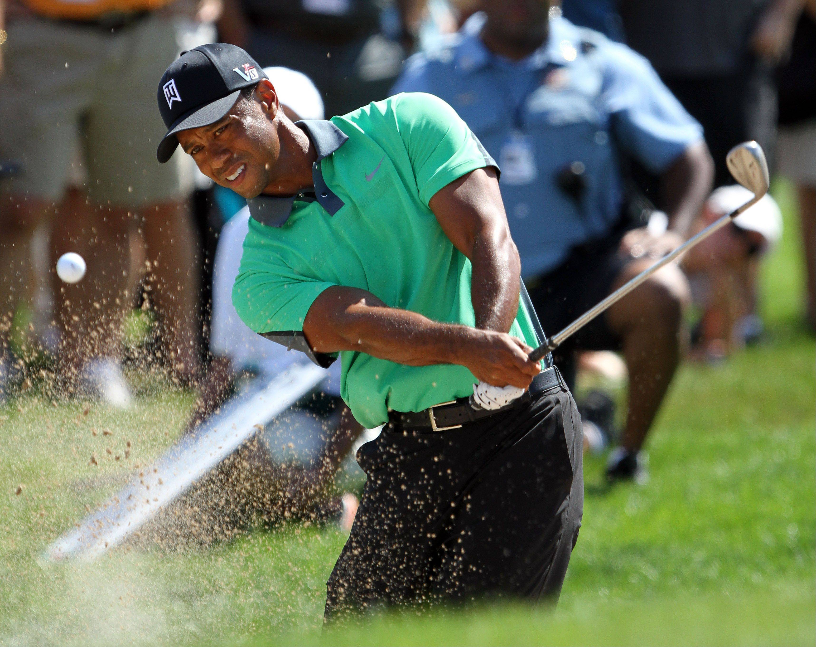 Tiger Woods hits out of the trap on the 13th hole.