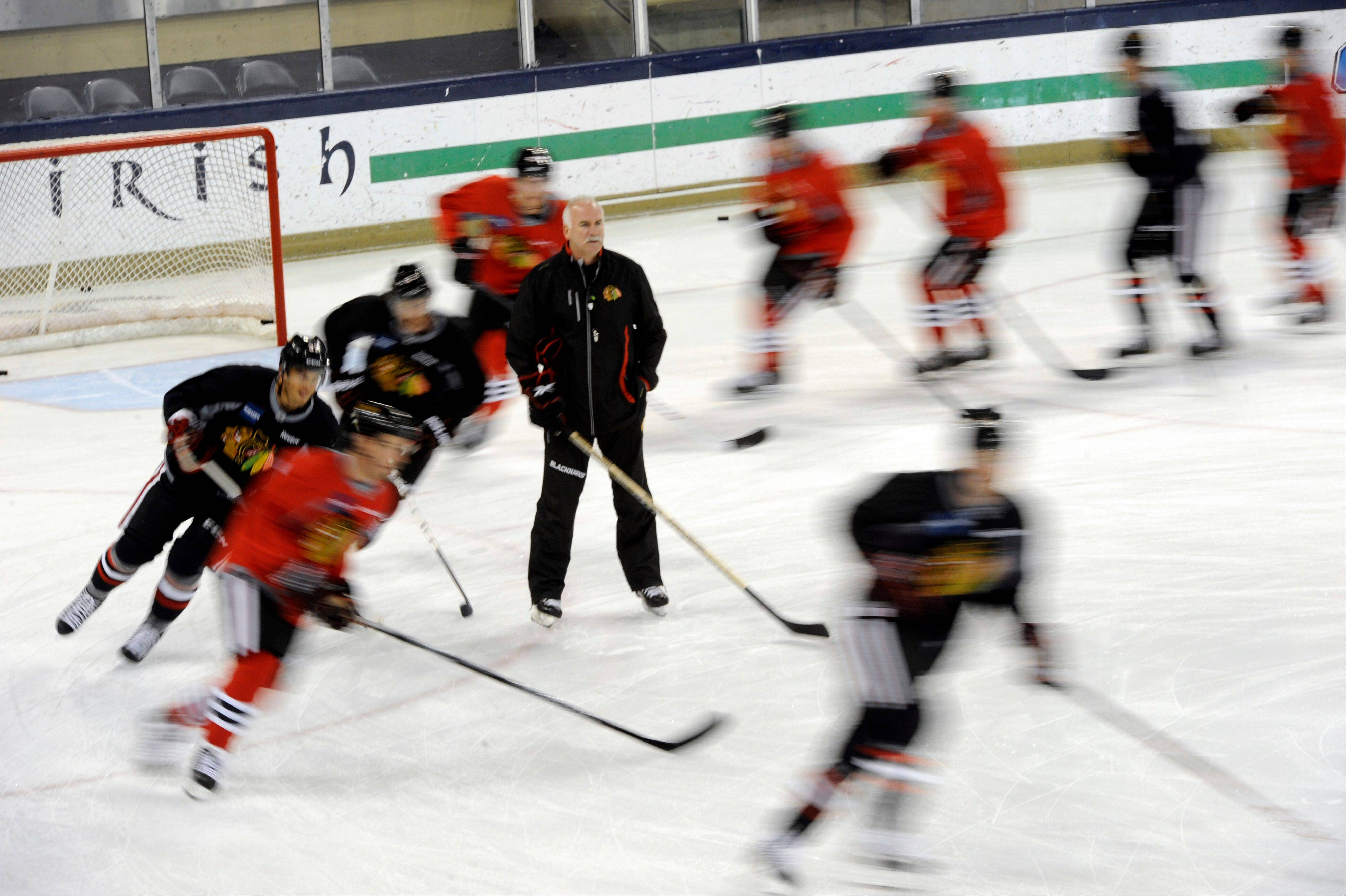 The Blackhawks are a blur as they skate past head coach Joel Quenneville at start of training camp Thursday.