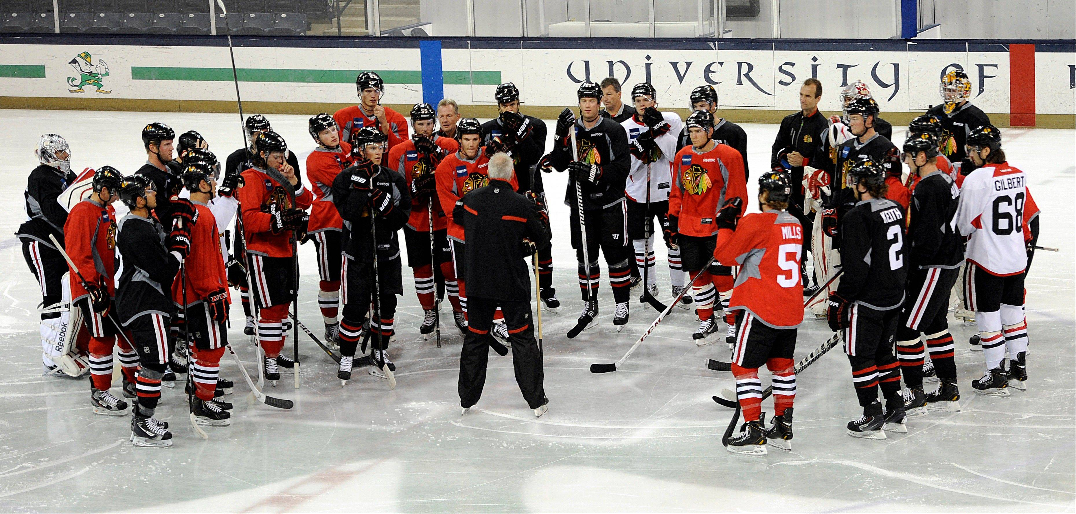 Blackhawks coach Joel Quenneville talks to his players as the defending Stanley Cup champions open training camp Thursday on the campus of the University of Notre Dame.