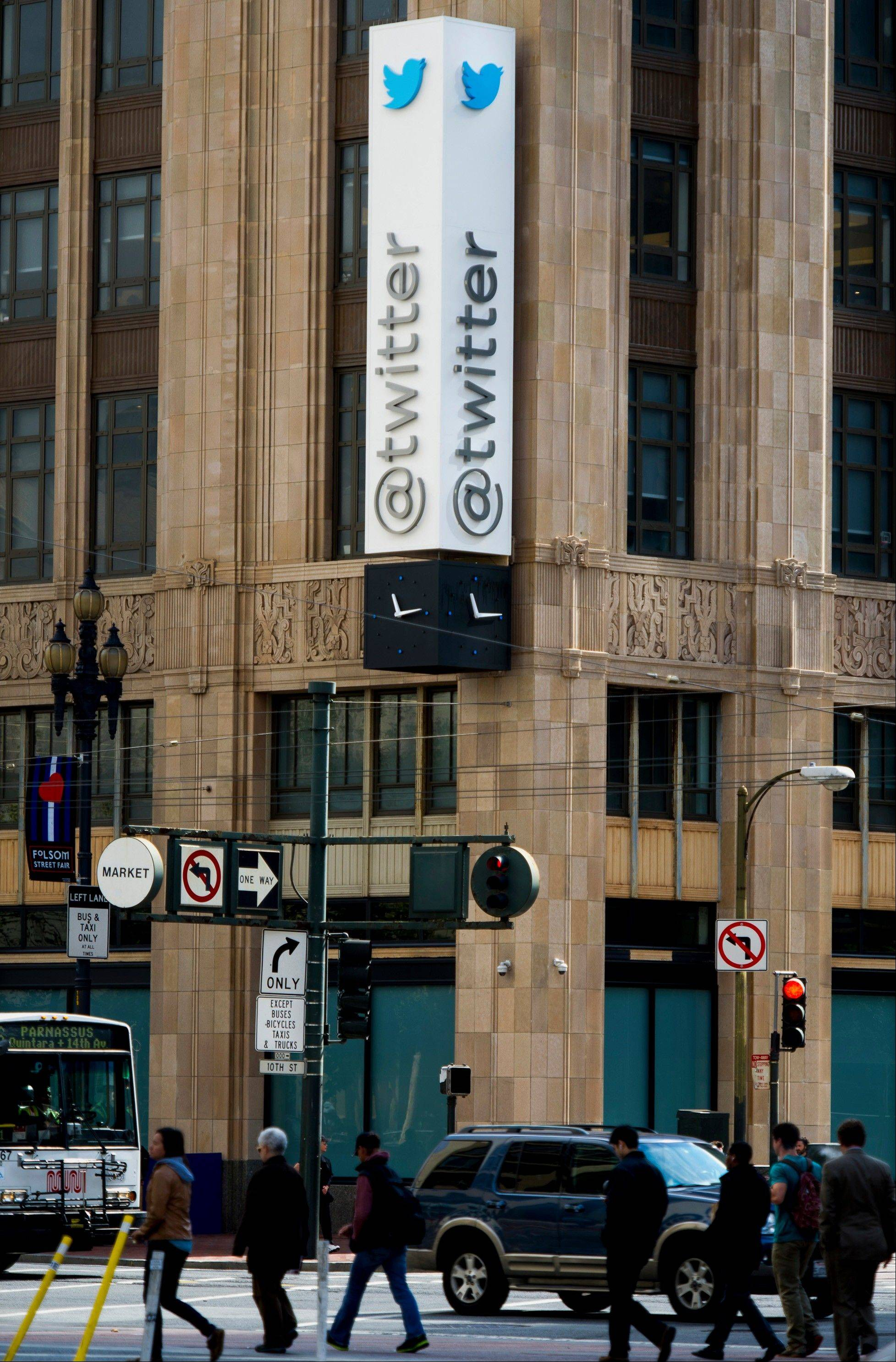 Pedestrians walk past Twitter Inc. headquarters Friday in San Francisco.