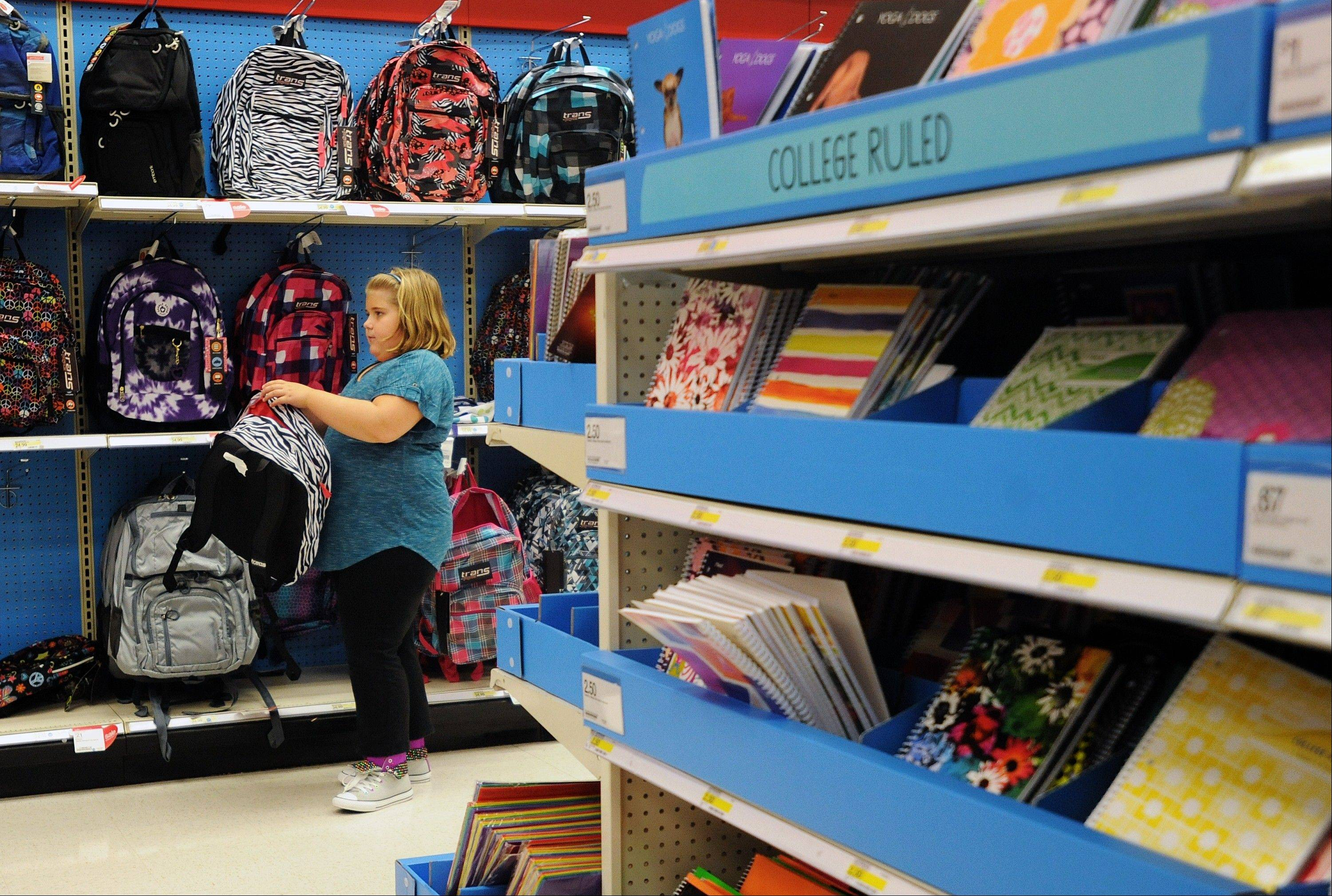 Raegan Jackson, 10, picks out a backpack shopping at Target in Lynchburg, Va. Americans boosted their spending at retail businesses only modestly in August, indicating that economic growth remains sluggish. Consumers bought more cars, furniture and electronics last month but held back on most other purchases.