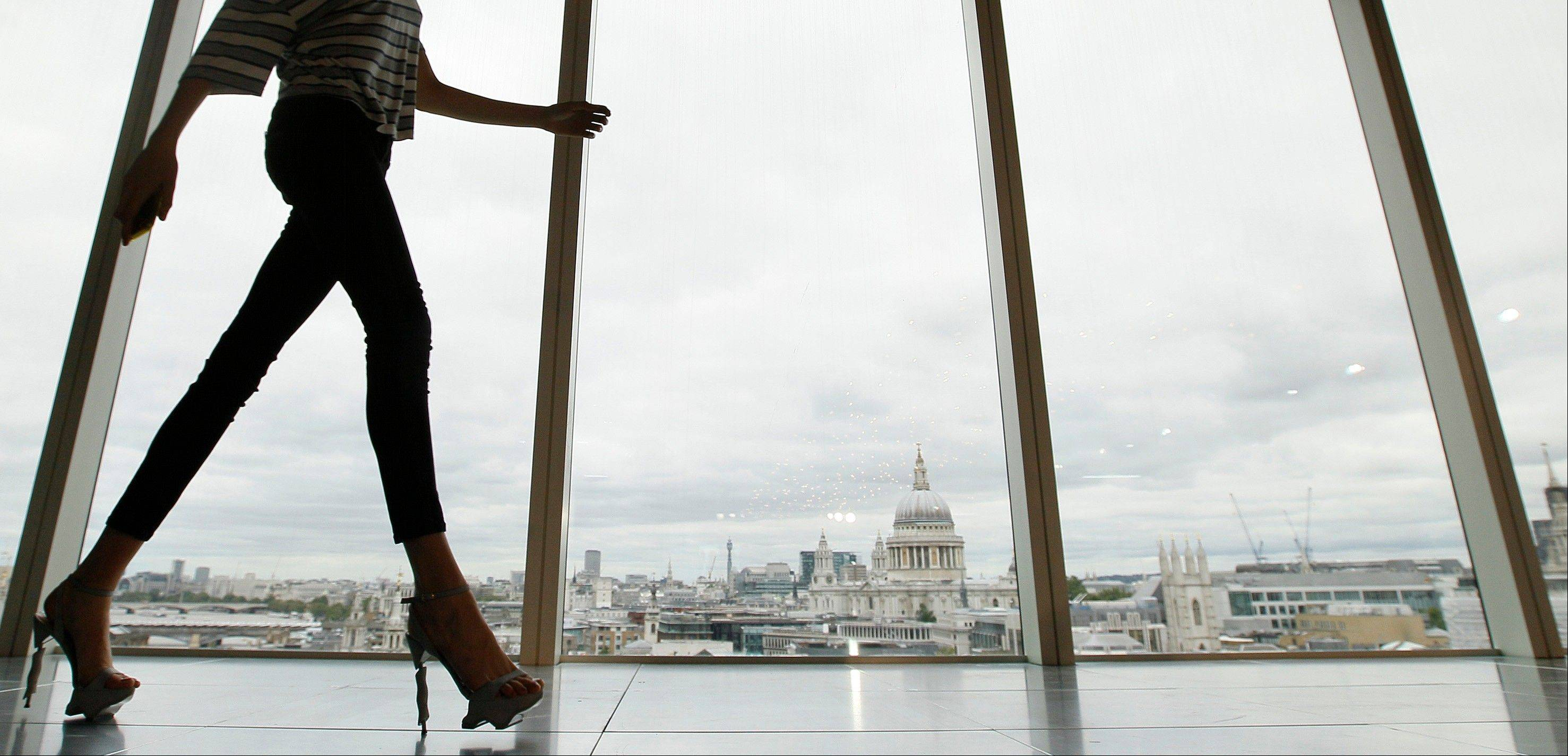 A model walks past a window with a view of St Paul's Cathedral in the background during the presentation of the Matthew Williamson Spring/Summer 2013 during London Fashion Week.