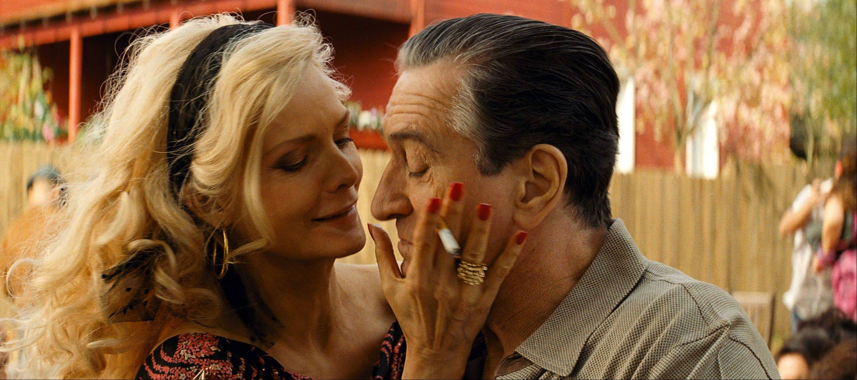 "Maggie (Michelle Pfeiffer) and Fred Blake (Robert DeNiro), aka mob boss turned snitch Giovanni Manzoni, share a touching moment in ""The Family."""
