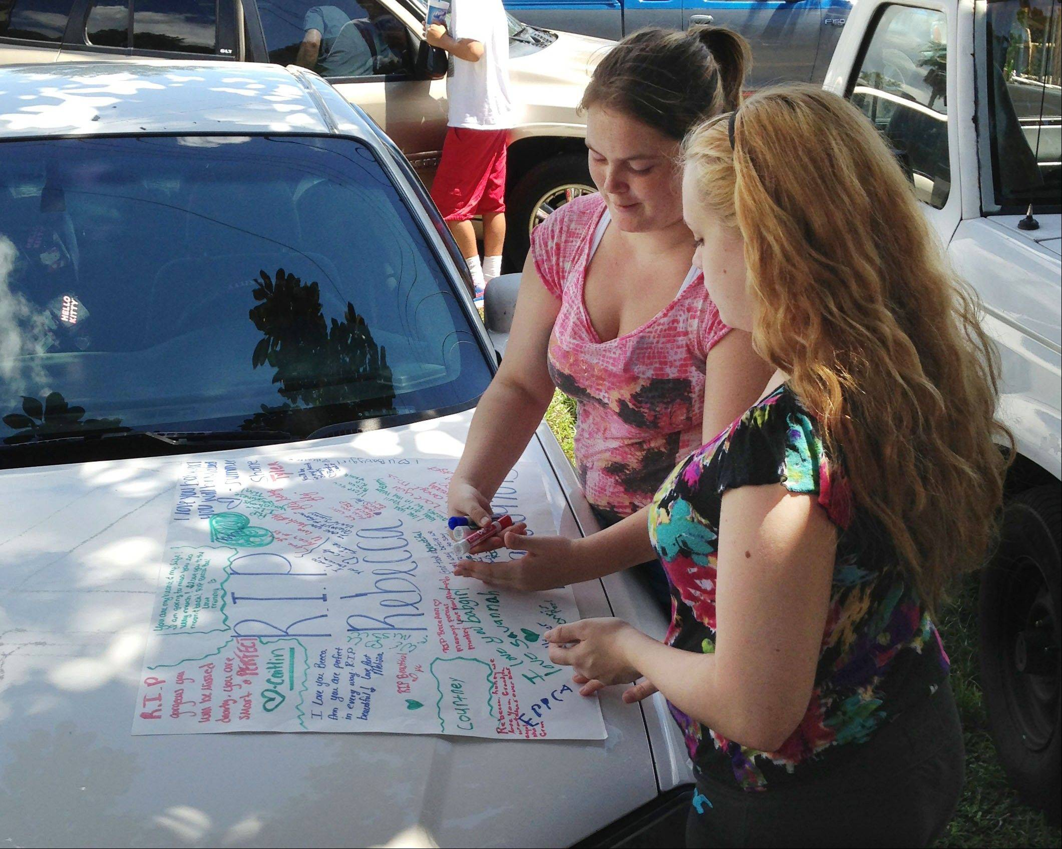 Summer Howard, 19 and Alecia Wilkins, 18, make a poster for Summer's sister Rebecca Sedwick. Polk County Sheriff Grady Judd said that Sedwick jumped to her death on on Monday at an old cement business in Lakeland, Fla.