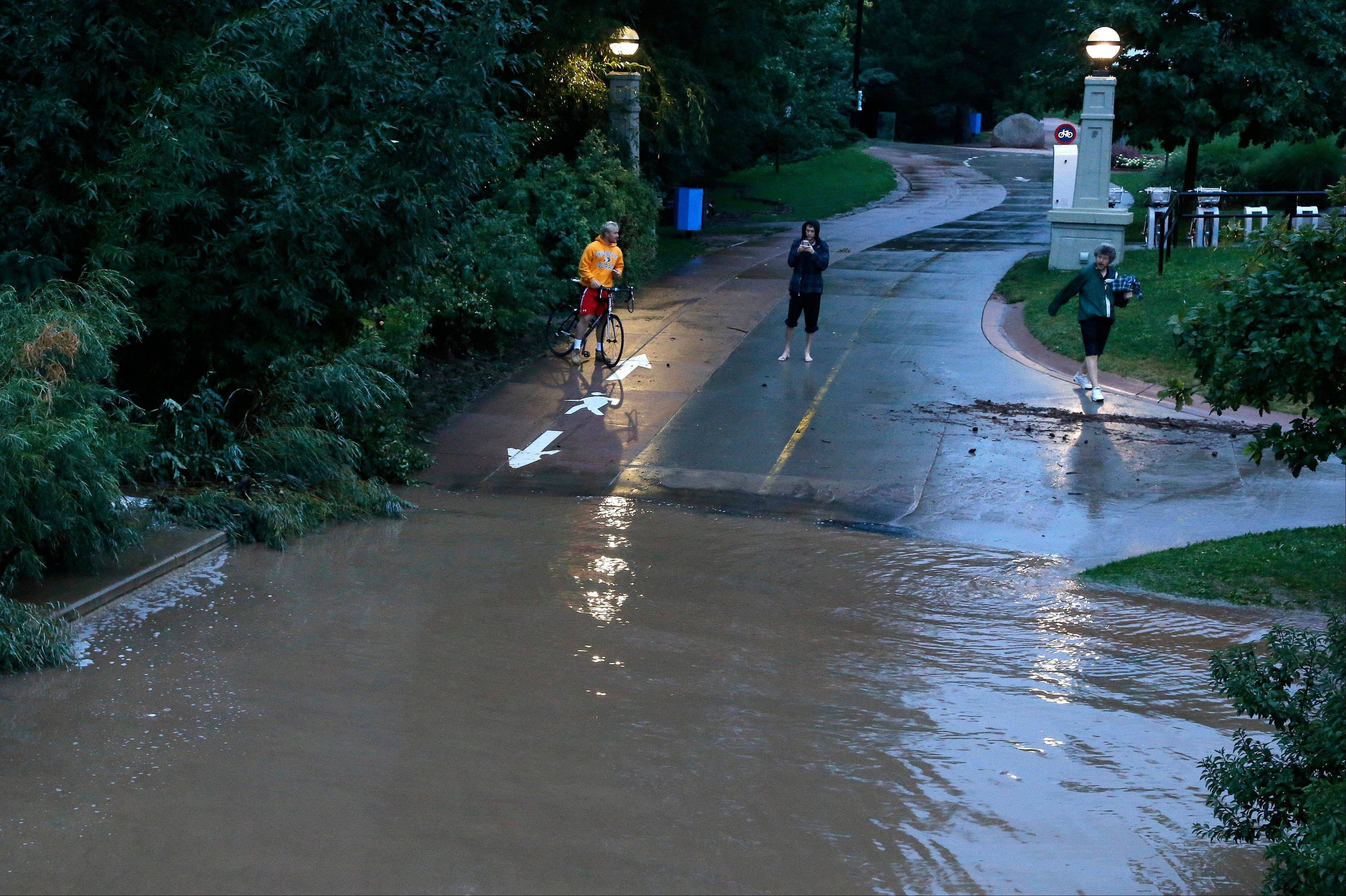 Local residents view dangerously high Boulder Creek following overnight flash flooding in downtown Boulder, Colo., Thursday, Sept 12, 2013. Flash flooding in Colorado has left two people dead and the widespread high waters are keeping search and rescue teams from reaching stranded residents and motorists in Boulder and nearby mountain communities as heavy rains hammered northern Colorado.