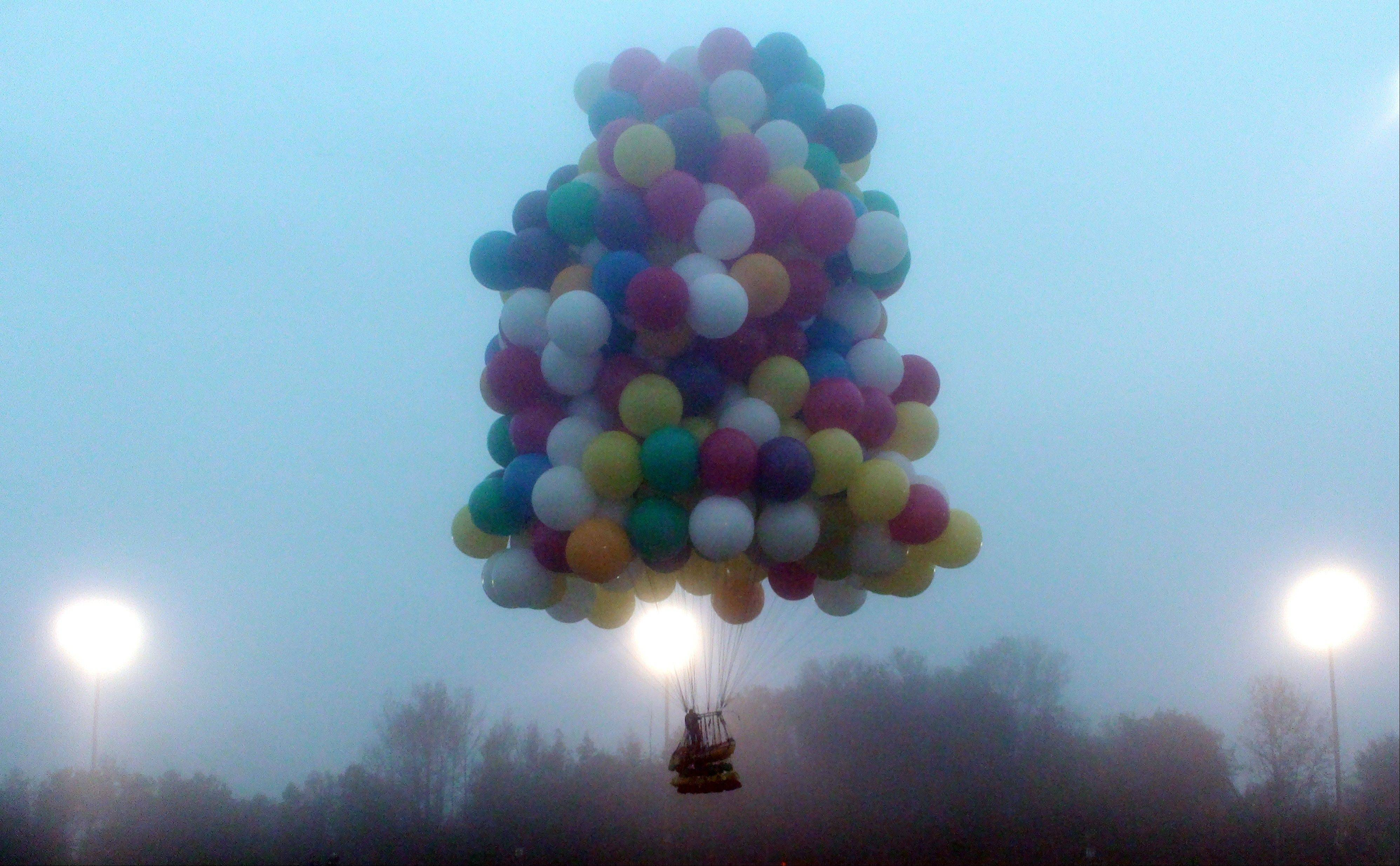 A balloon cluster carrying Jonathan Trappe lifts off from Caribou, Maine, Thursday, Sept. 12, 2013. Trappe lifted off Thursday using hundreds of helium-filled balloons clustered together. Trappe hoped to be the first person to successfully complete a trans-Atlantic flight using the balloon cluster, but he landed short of his goal in Newfoundland.