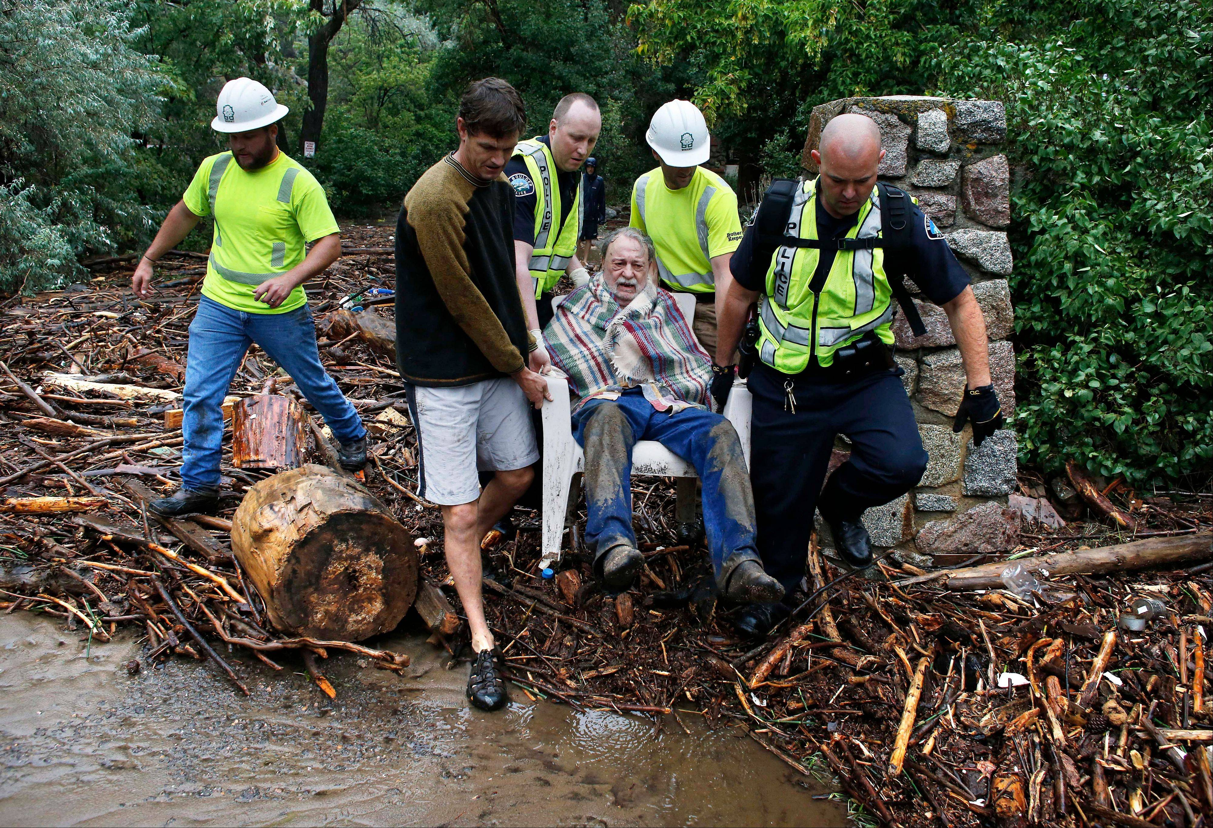 Will Pitner is rescued by emergency workers, and neighbor Jeff Writer, left, after a night trapped sheltering outside on high ground above his home as it filled with water from a surge of water, after days of record rain and flooding, at the base of Boulder Canyon, Colo., Friday Sept. 13, 2013 in Boulder. Flash flooding in Colorado has left at least three people reportedly dead and the widespread high waters have hampered emergency workers' access to affected communities as heavy rains hammered northern Colorado.