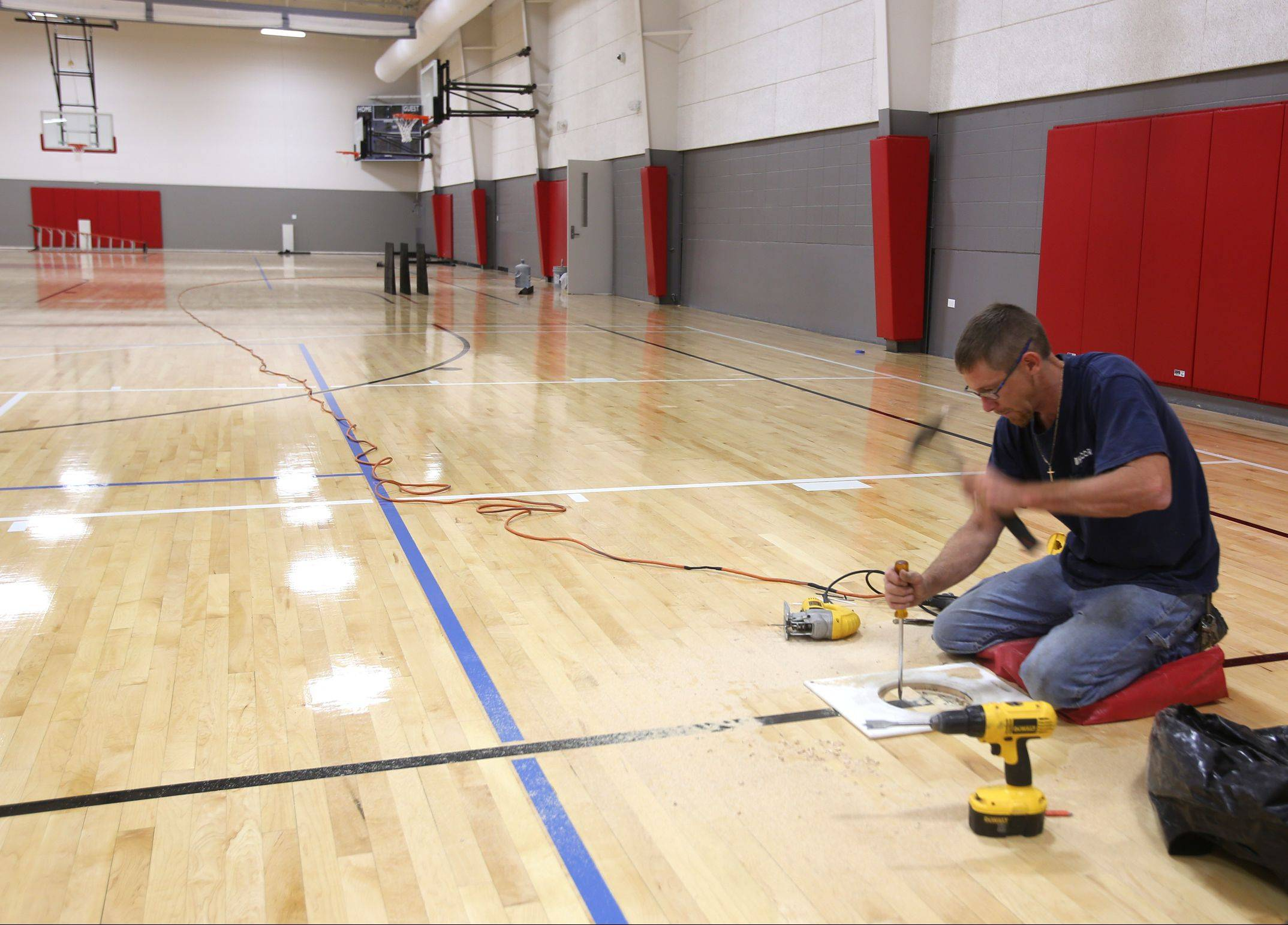 A new volleyball/basketball court is readied Thursday by carpenter Jeremy Cavanagh in advance of the grand reopening of the Glendale Heights Sports Hub this weekend.