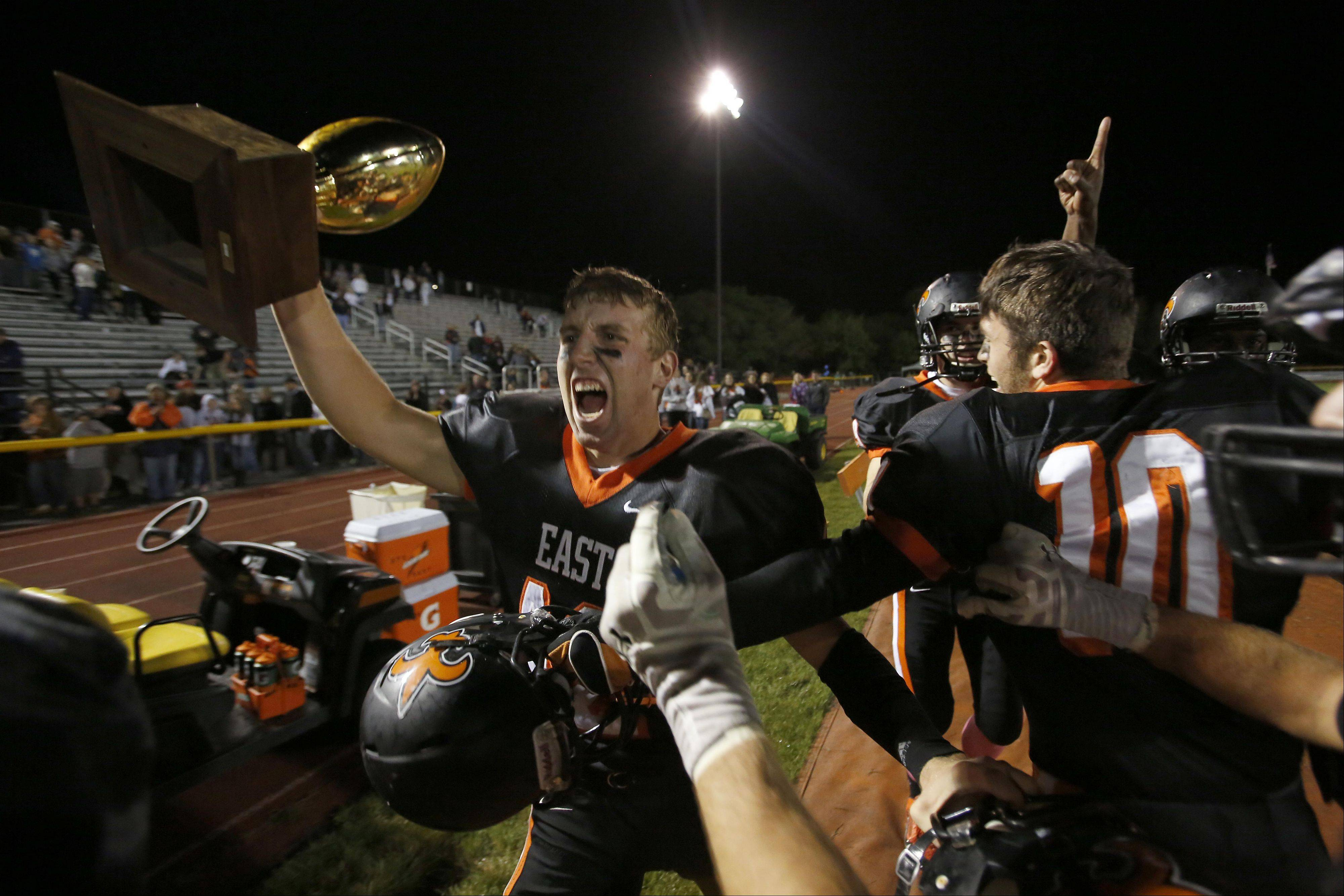 St. Charles East's Vince Locascio hoists the trophy after the Saints won in overtime against St. Charles North .
