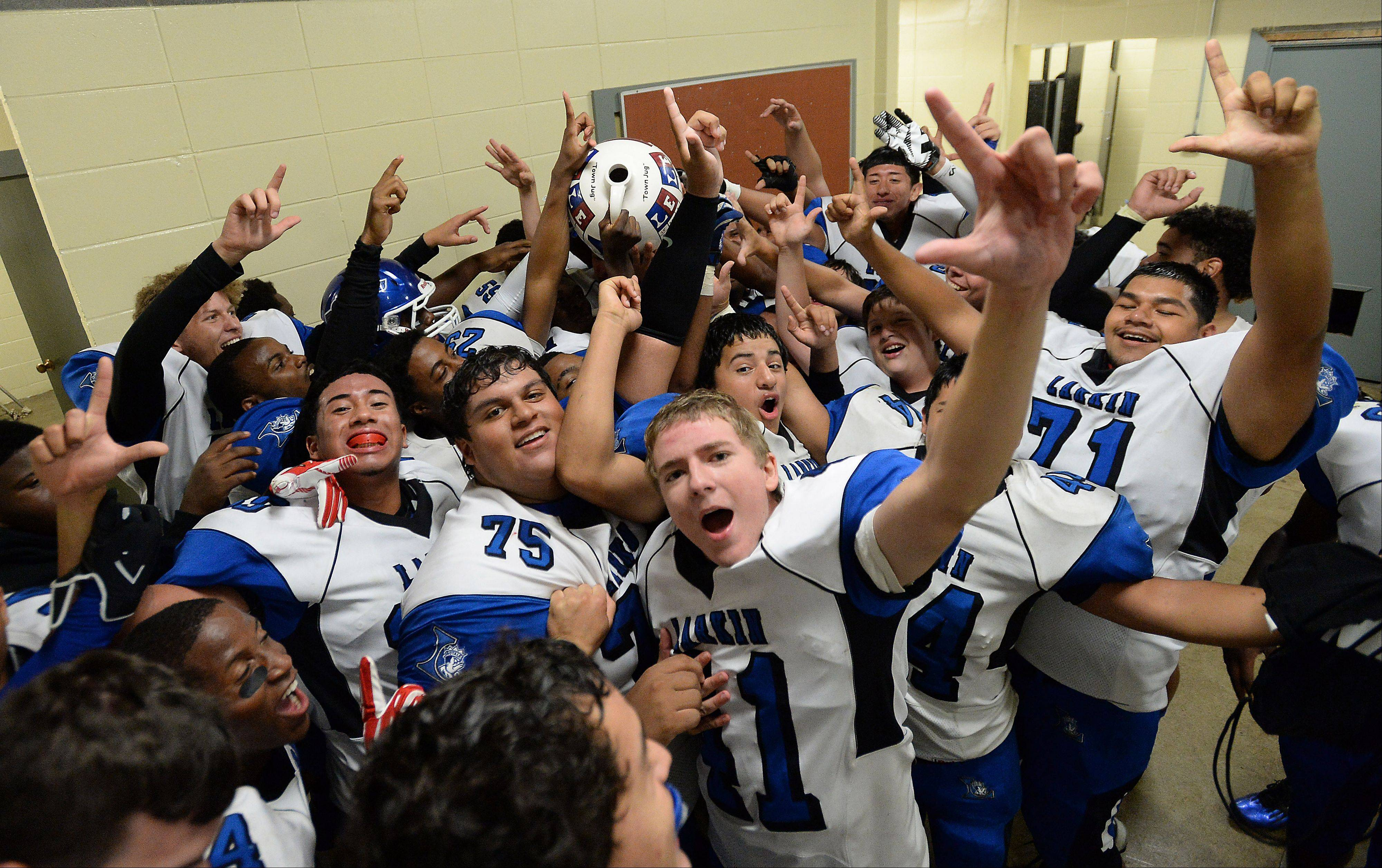"Larkin's locker room explodes with excitement after beating Elgin and claiming the ""Jug"" in the varsity football matchup at Elgin High School on Friday."