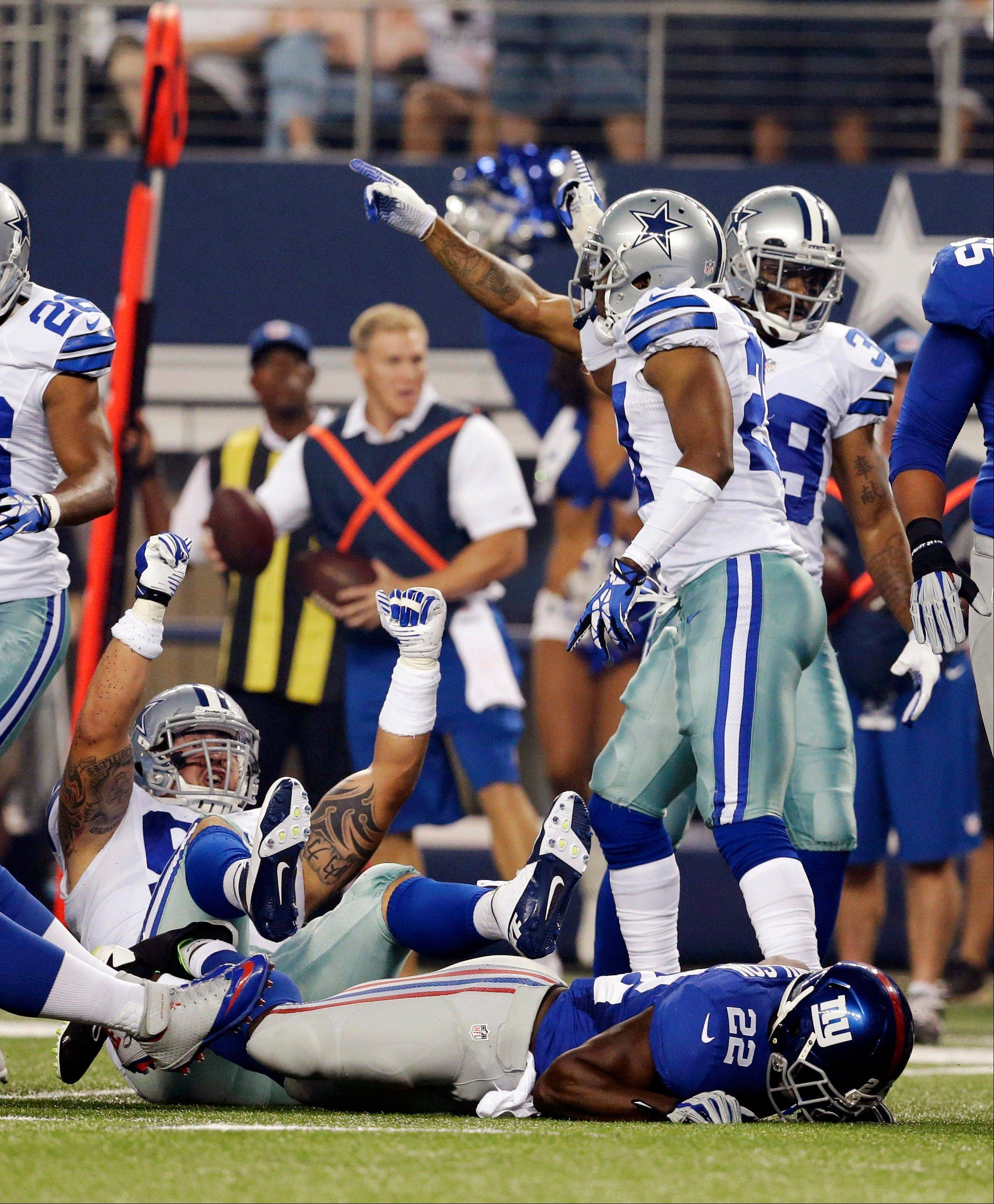 The Cowboys celebrate after recovering a fumble by Giants running back David Wilson during the first half Sunday in Arlington, Texas.