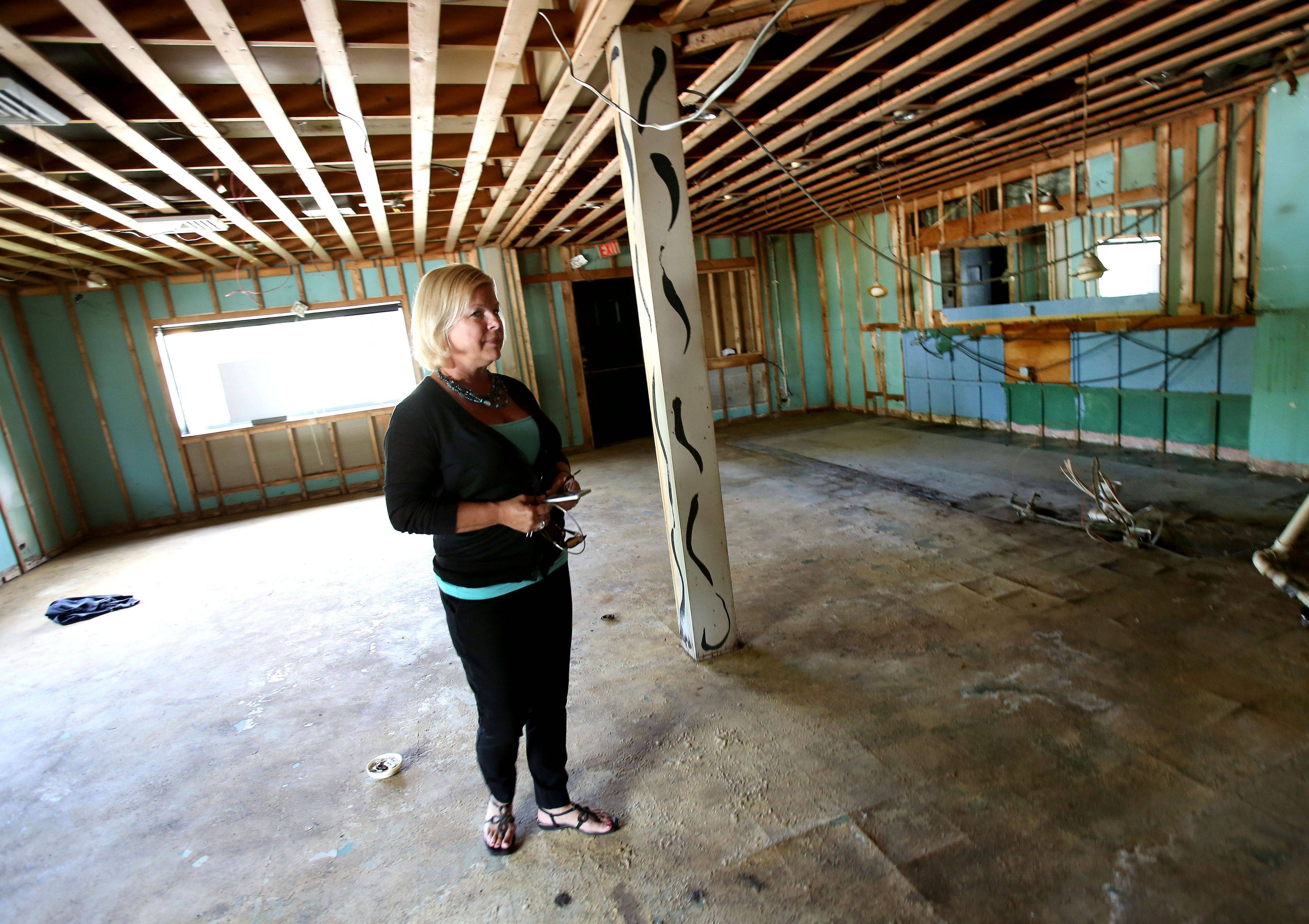 Jerri Nolan, owner of Raymes Steak and Fish House in Lisle, looks around the old building that was so severely flooded in April it can't be repaired. A new restaurant will be built on an adjacent lot.
