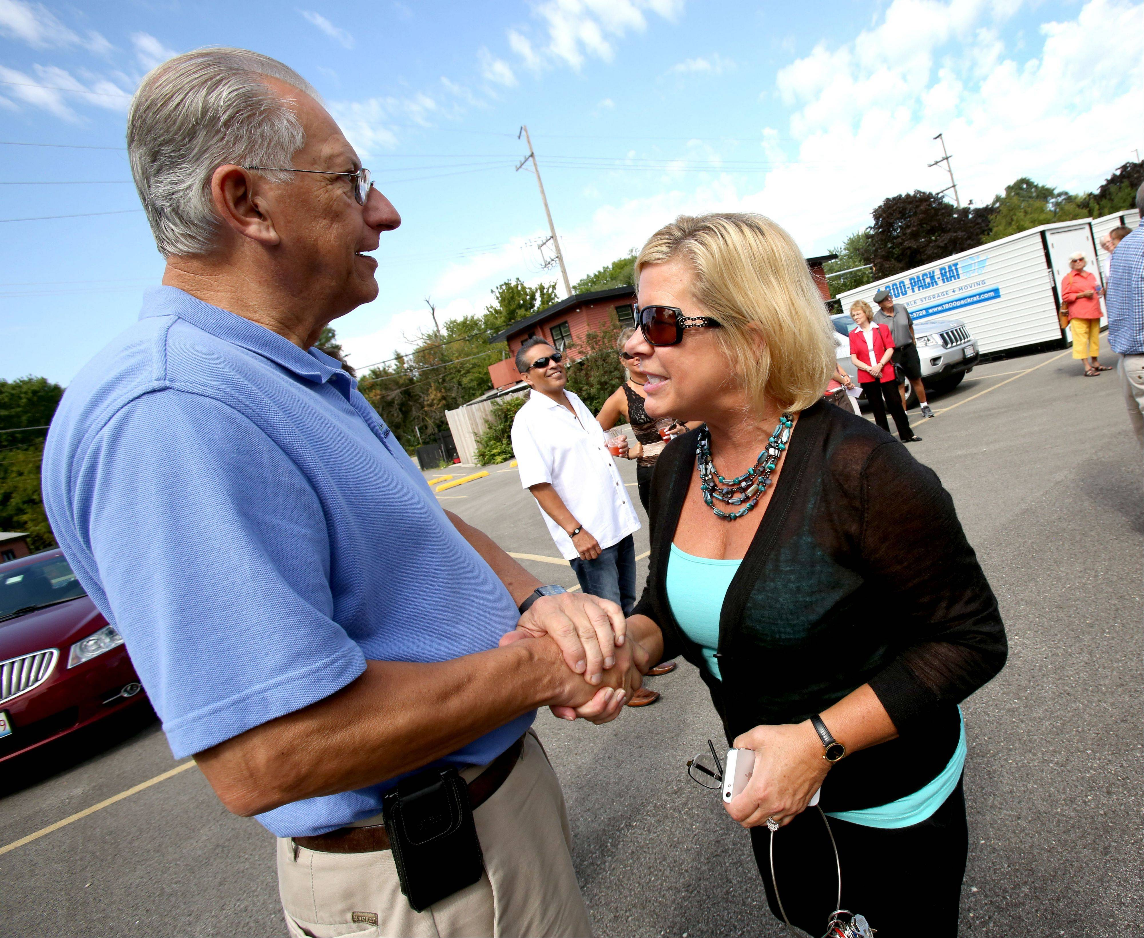 Lisle Mayor Joe Broda congratulates Raymes Steak and Fish House owner Jerri Nolan on Thursday before a ceremonial groundbreaking for the restaurant's new building. The old building was damaged beyond repair by flooding April 18.