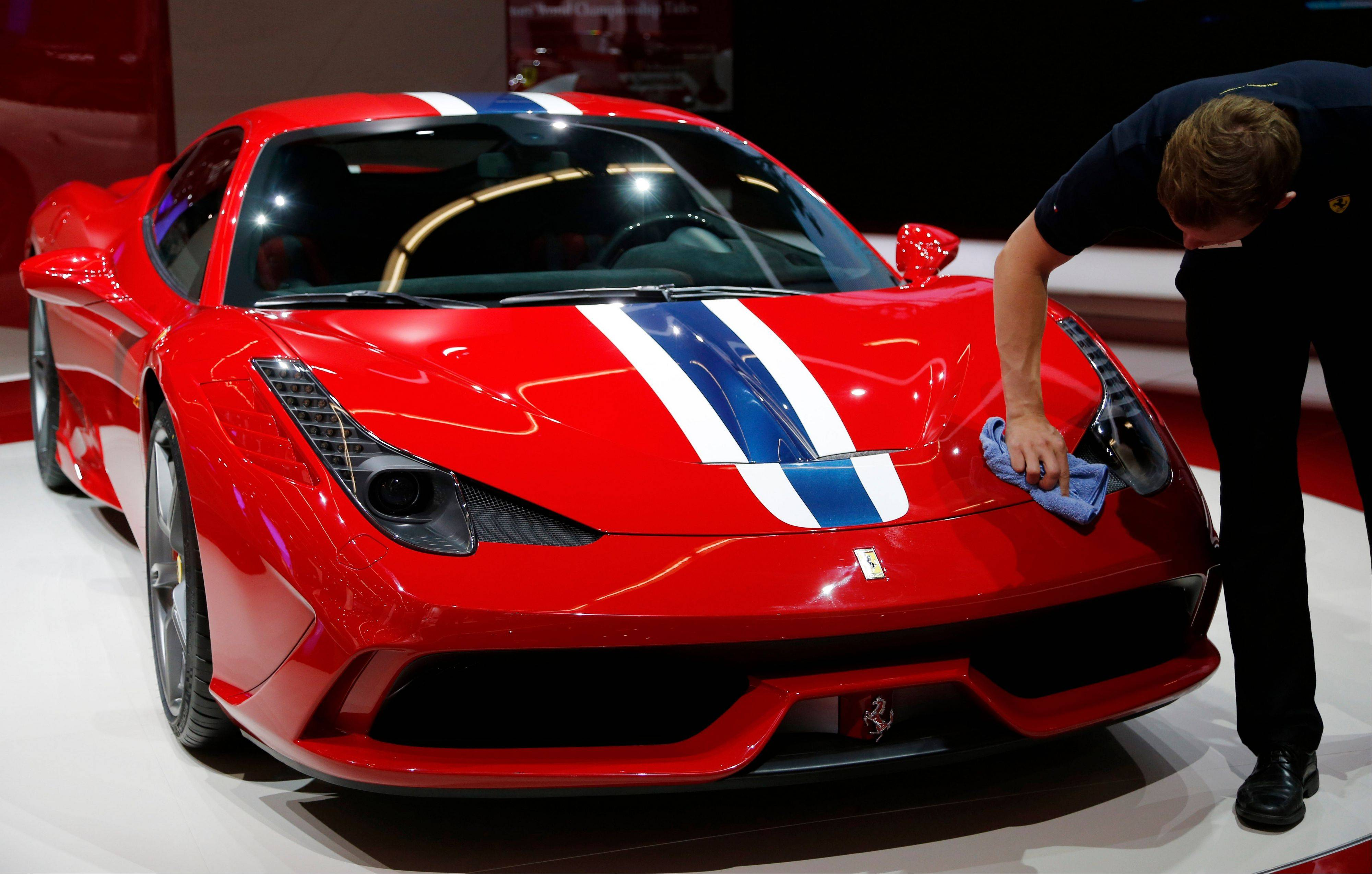 A man cleans a Ferrari 458 Speciale during the second press day of the 65th Frankfurt Auto Show in Frankfurt, Germany.