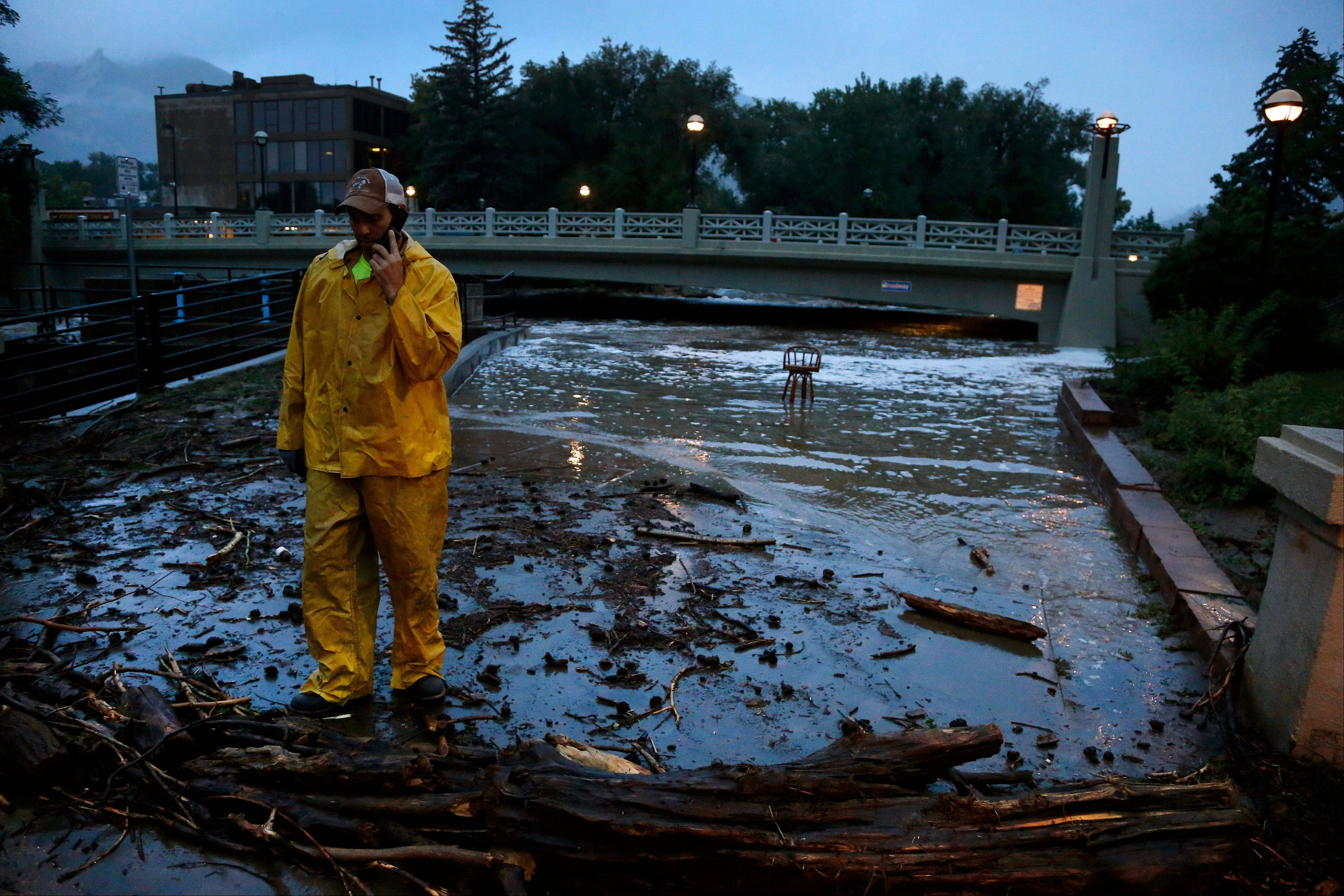 A city worker talks on his phone while surveying high water levels on Boulder Creek following overnight flash flooding in downtown Boulder, Colo., Thursday, Sept 12, 2013. Flash flooding in Colorado has left two people dead and the widespread high waters are keeping search and rescue teams from reaching stranded residents and motorists in Boulder and nearby mountain communities as heavy rains hammered northern Colorado.