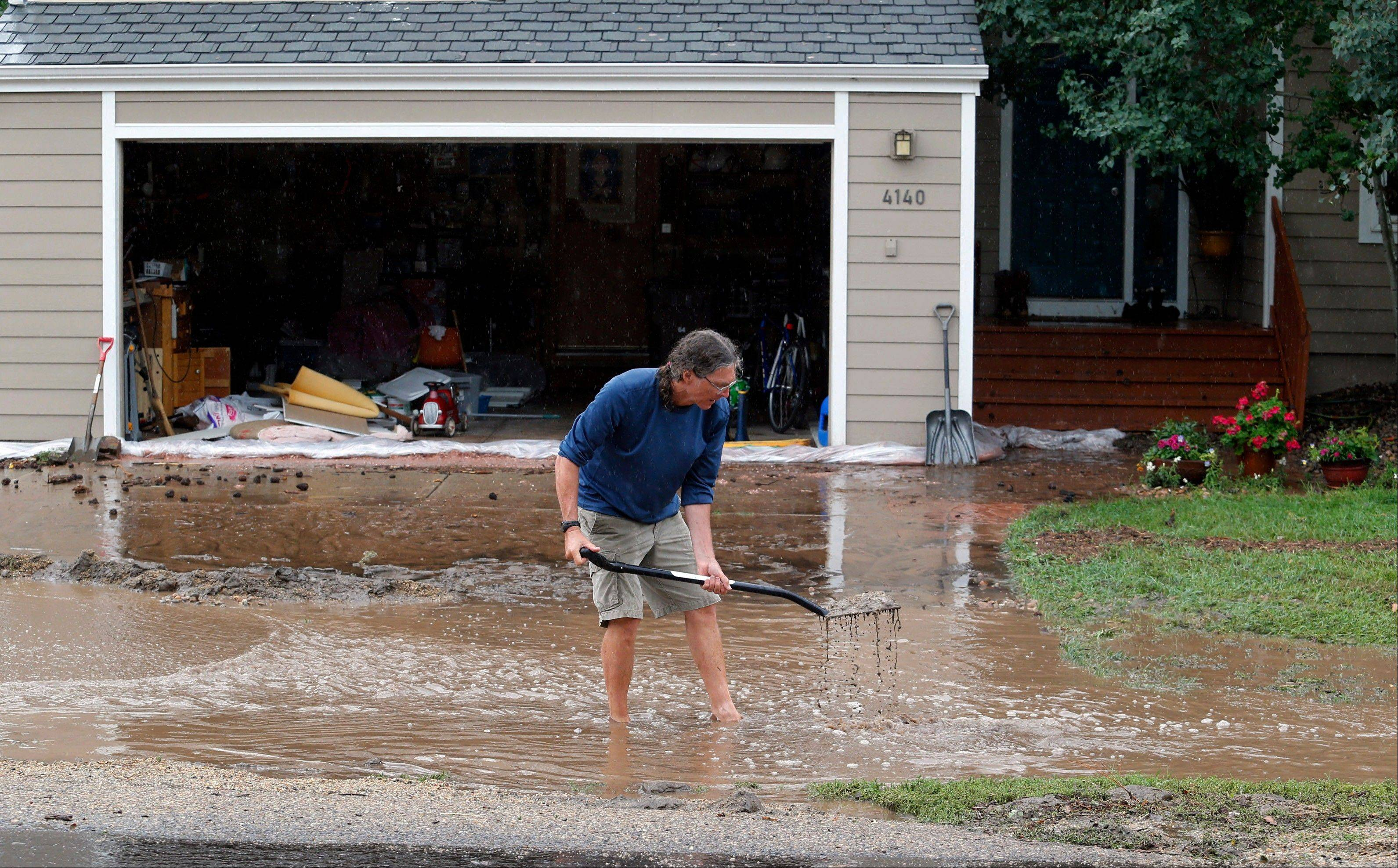 Brian Flynn, of Oregon, clears a drain in front of his sister's home in Boulder, Colo., on Thursday, Sept. 12, 2013. Flash flooding in Colorado has cut off access to towns, closed the University of Colorado in Boulder and left at least three people dead.