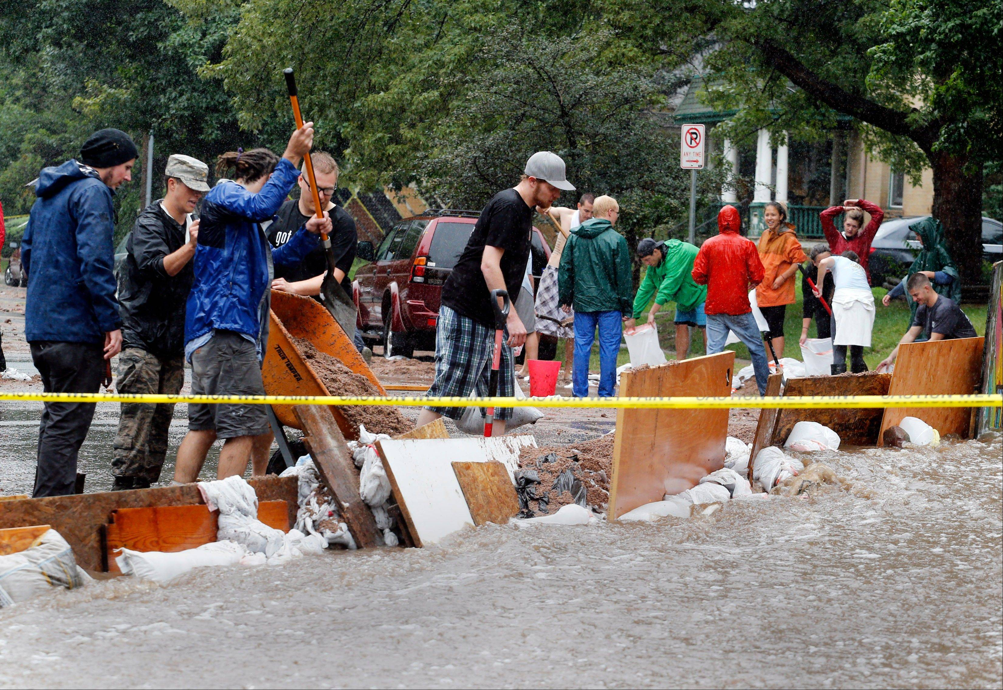 Residence of an apartment house work to divert flood water from their building in Boulder, Colo., on Thursday, Sept. 12, 2013. Flash flooding in Colorado has cut off access to towns, closed the University of Colorado in Boulder and left at least three people dead.