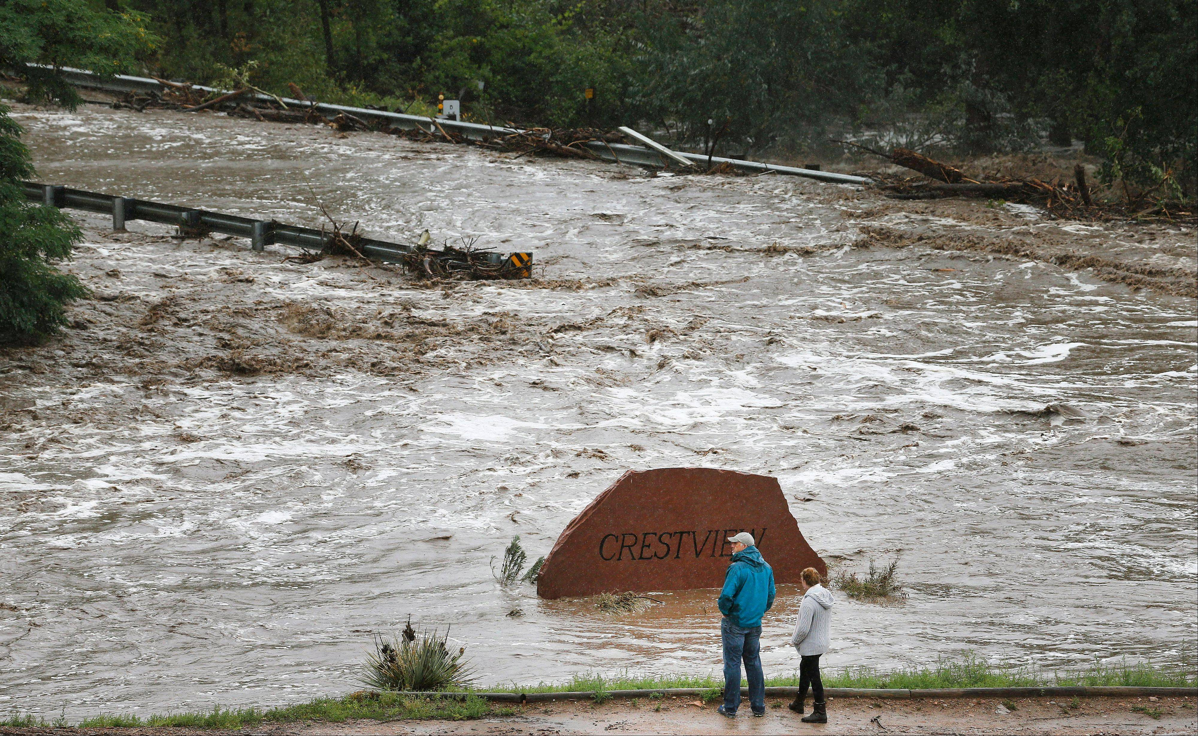 Local residents look over a road washed out by a torrent of water following overnight flash flooding near Left Hand Canyon, south of Lyons, Colo., Thursday, Sept 12, 2013. The widespread high waters are keeping search and rescue teams from reaching stranded residents in Lyons and nearby mountain communities as heavy rains hammered northern Colorado
