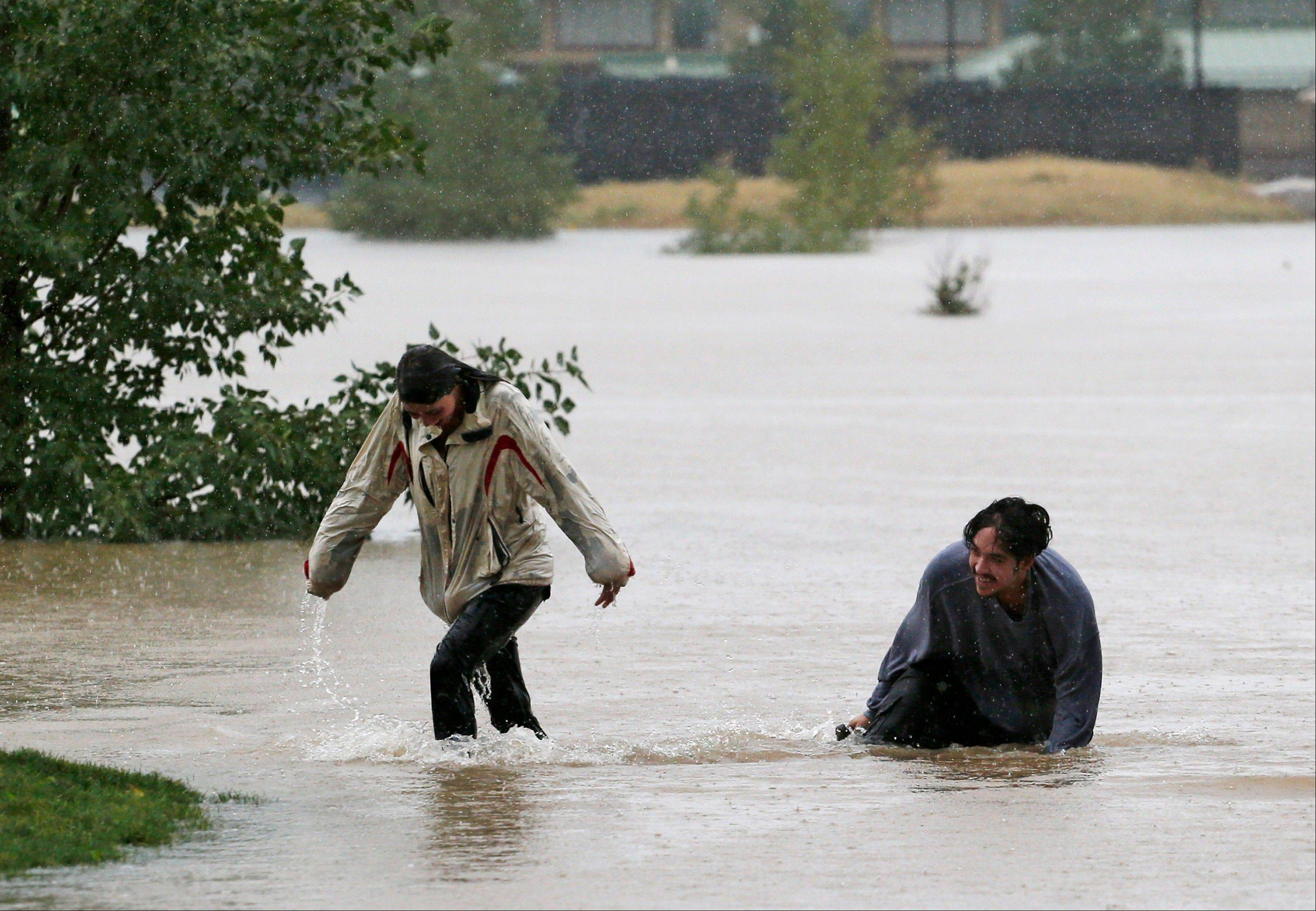 A couple plays in flood water at Utah Park in Aurora, Colo., on Thursday, Sept. 12, 2013. The park was under water due to flooding. Flash flooding in Colorado has cut off access to towns, closed the University of Colorado in Boulder and left at least three people dead.