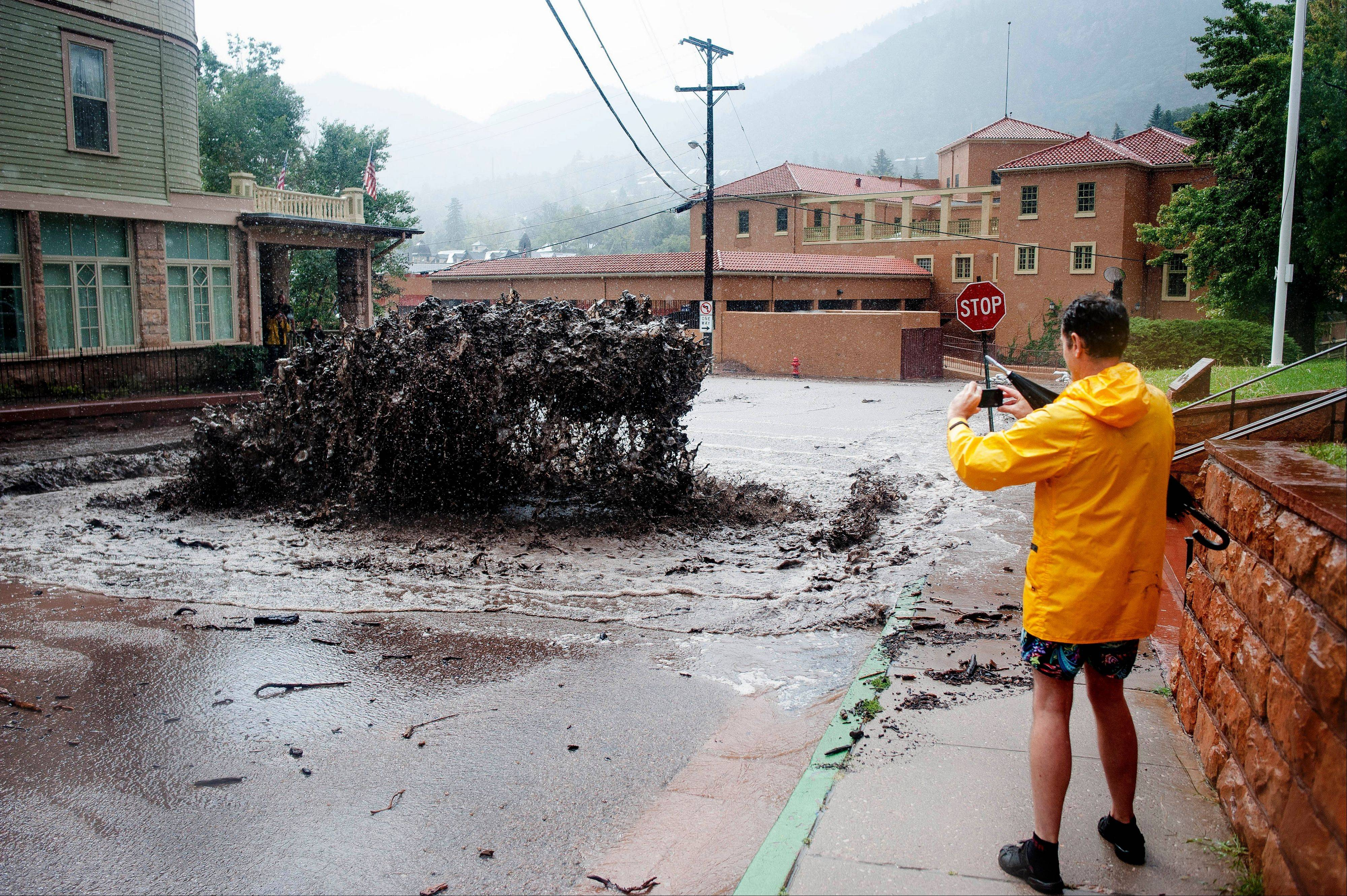 John Shada, of Manitou Springs, Colo., takes a photo of flood water as it shoots out of a sewer on Canon Avenue on Thursday, Sept. 12, 2013, in Manitou Springs, Colo. Flash flooding in Colorado has cut off access to towns, closed the University of Colorado in Boulder and left at least three people dead.