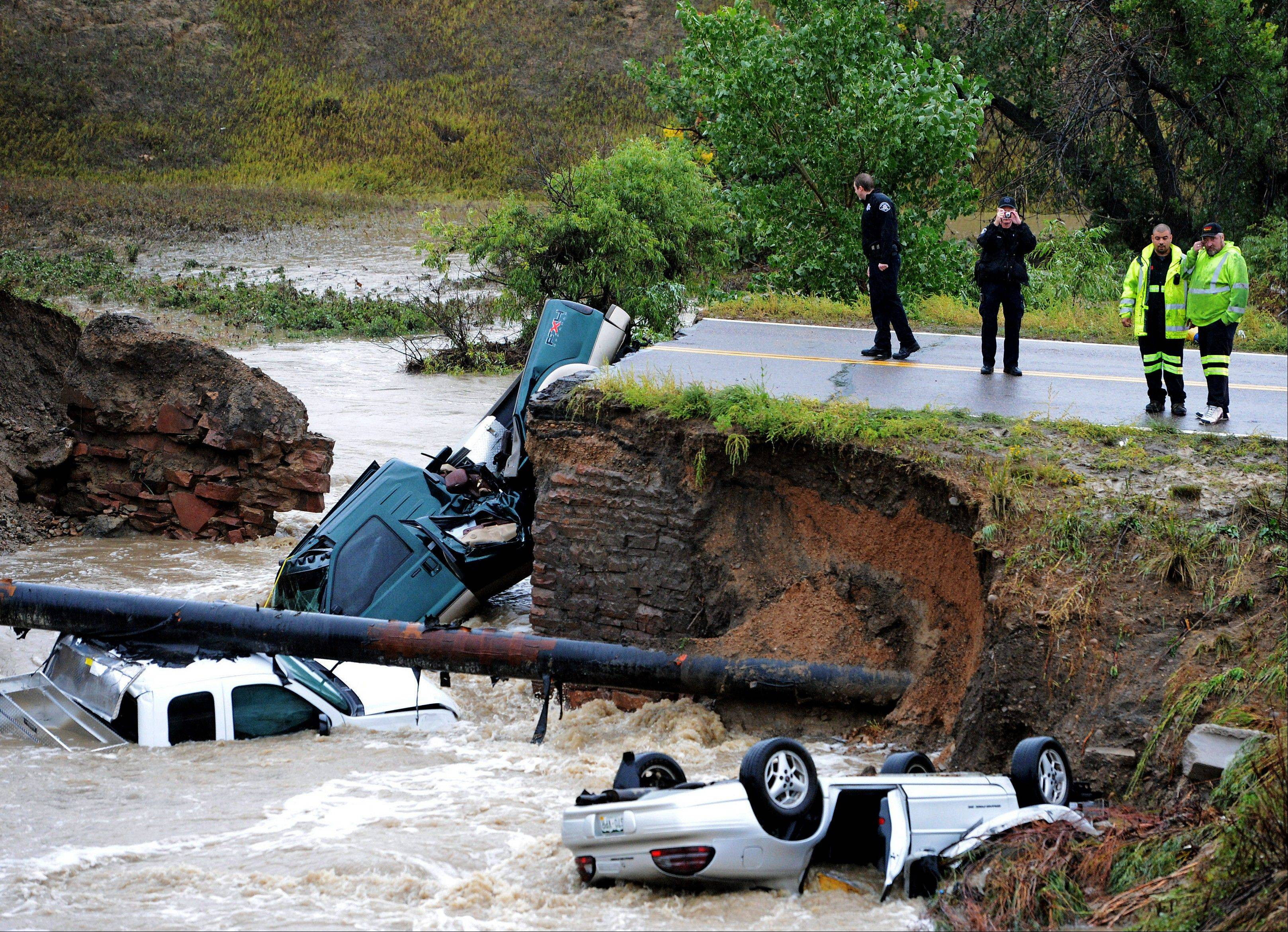 "Officials investigate the scene of a road collapse at Highway 287 and Dillon at the Broomfield/Lafayette border, Colo., that sent three vehicles into the water after flash flooding on Thursday, Sept. 12, 2013. The National Weather Service has warned of an ""extremely dangerous and life-threatening situation"" throughout the region."