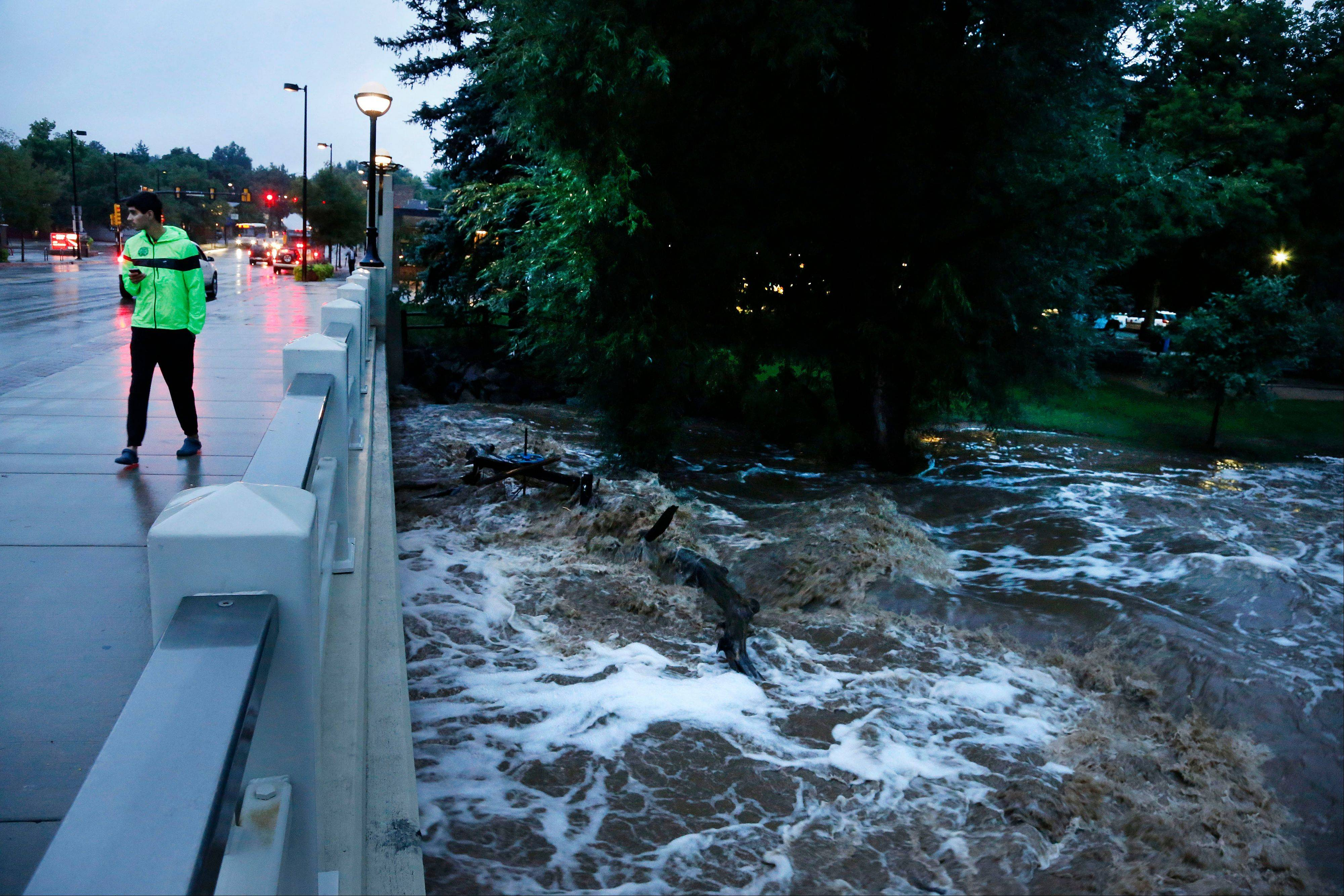A man walks past dangerously high Boulder Creek following overnight flash flooding in downtown Boulder, Colo., Thursday, Sept 12, 2013. Flash flooding in Colorado has left two people dead and the widespread high waters are keeping search and rescue teams from reaching stranded residents and motorists in Boulder and nearby mountain communities as heavy rains hammered northern Colorado.