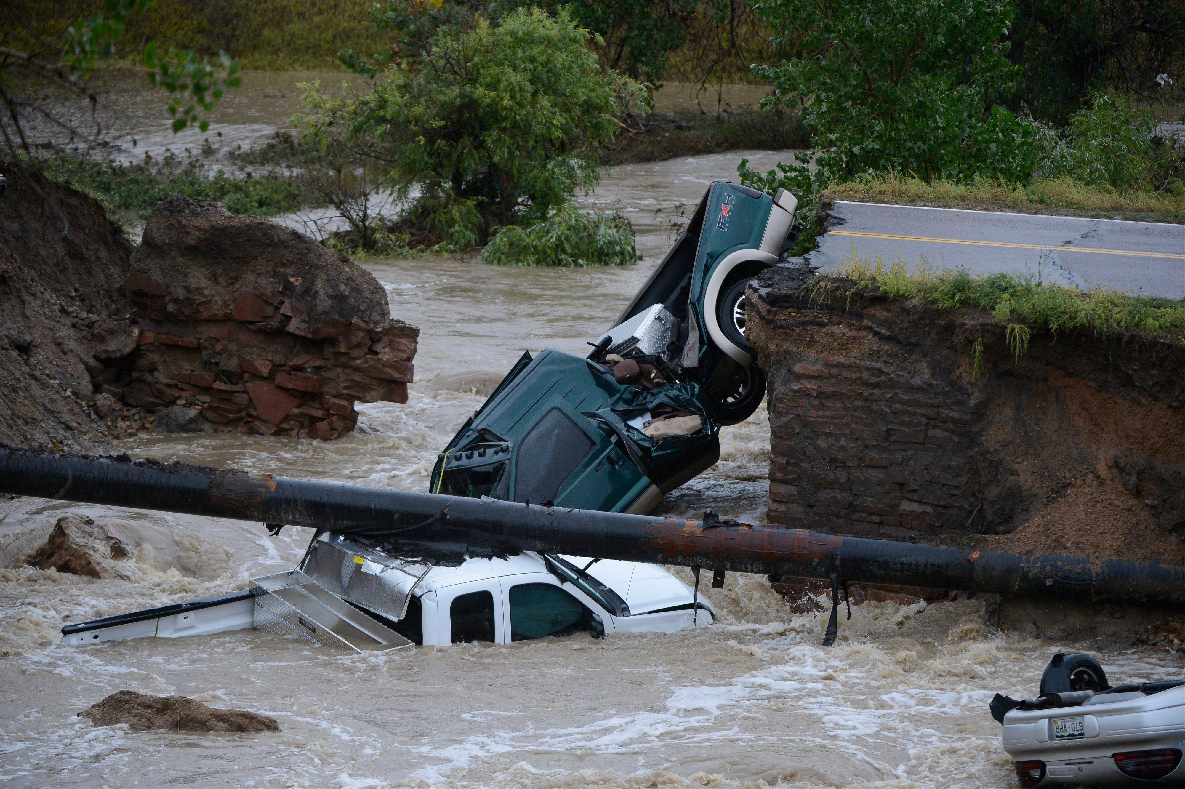Three vehicles crashed into a creek after the road washed out from beneath them near Dillon Rd. and 287 in Broomfield Colo., Thursday, Sept. 12, 2013 in heavy flooding. Three people were rescued.