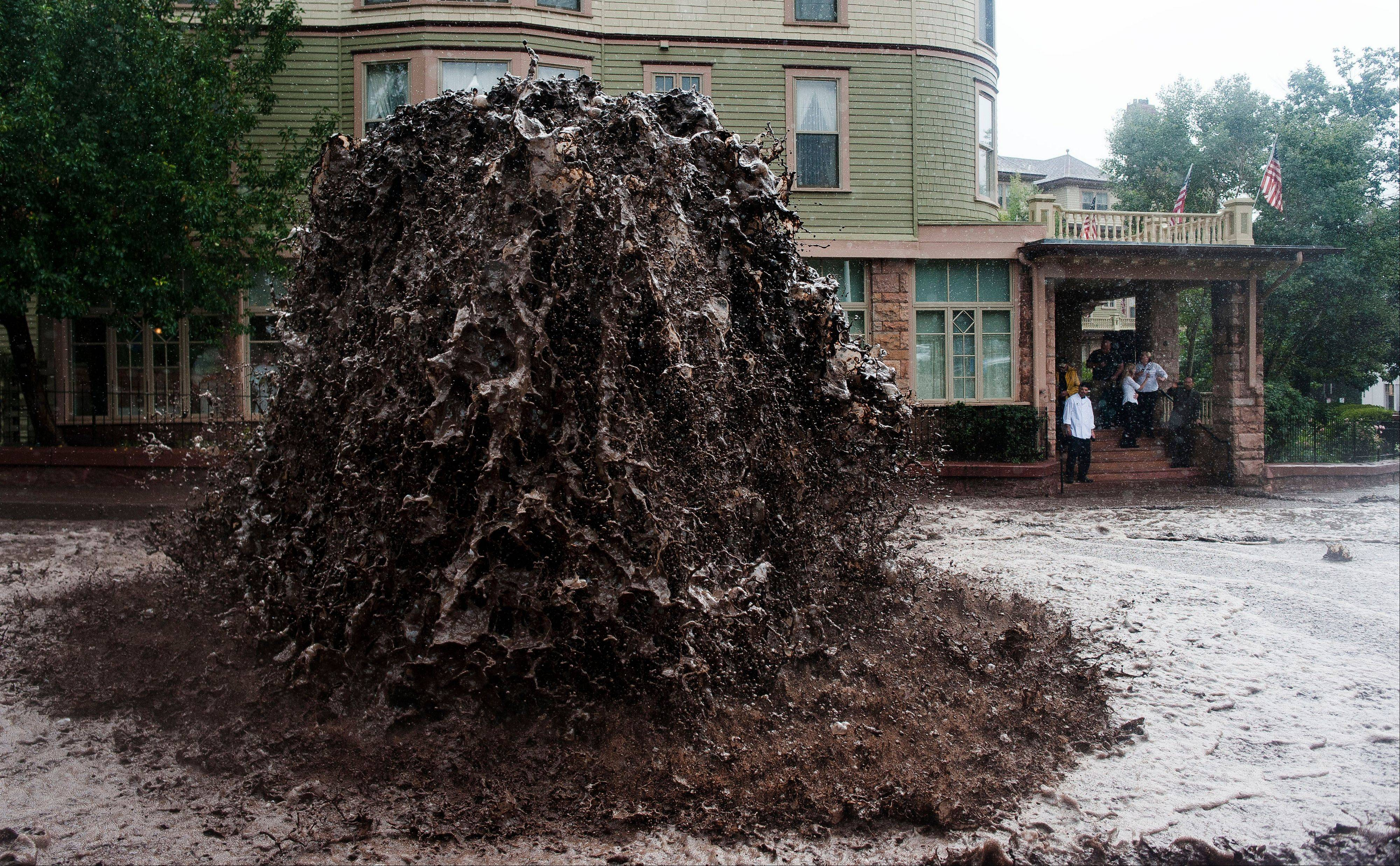 A geyser of flood water shoots out of a sewer on Canon Avenue next to the Cliff House in Manitou Springs, Colo. Thursday, Sept. 12, 2013 as storms continue to dump rain over the Waldo Canyon burn scar.