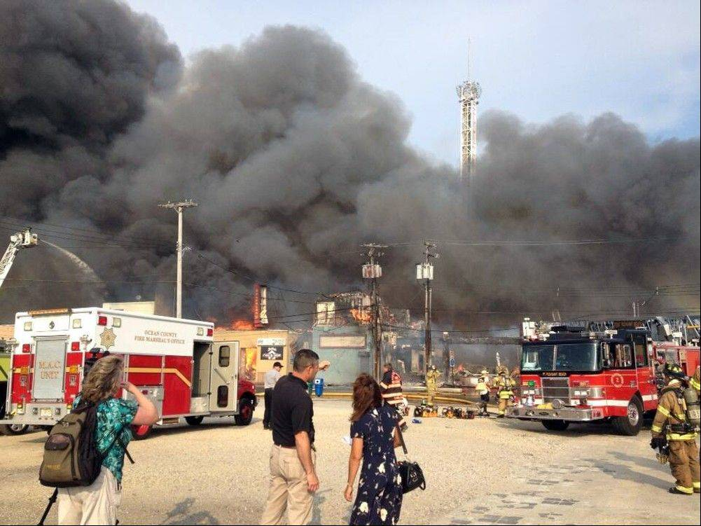 Firefighters battle a raging fire on the boardwalk in Seaside Heights, N.J. that apparently started in an ice cream shop and has spread several blocks down, Thursday, Sept. 12, 2013. The boardwalk was damaged in Superstorm Sandy and was being repaired.