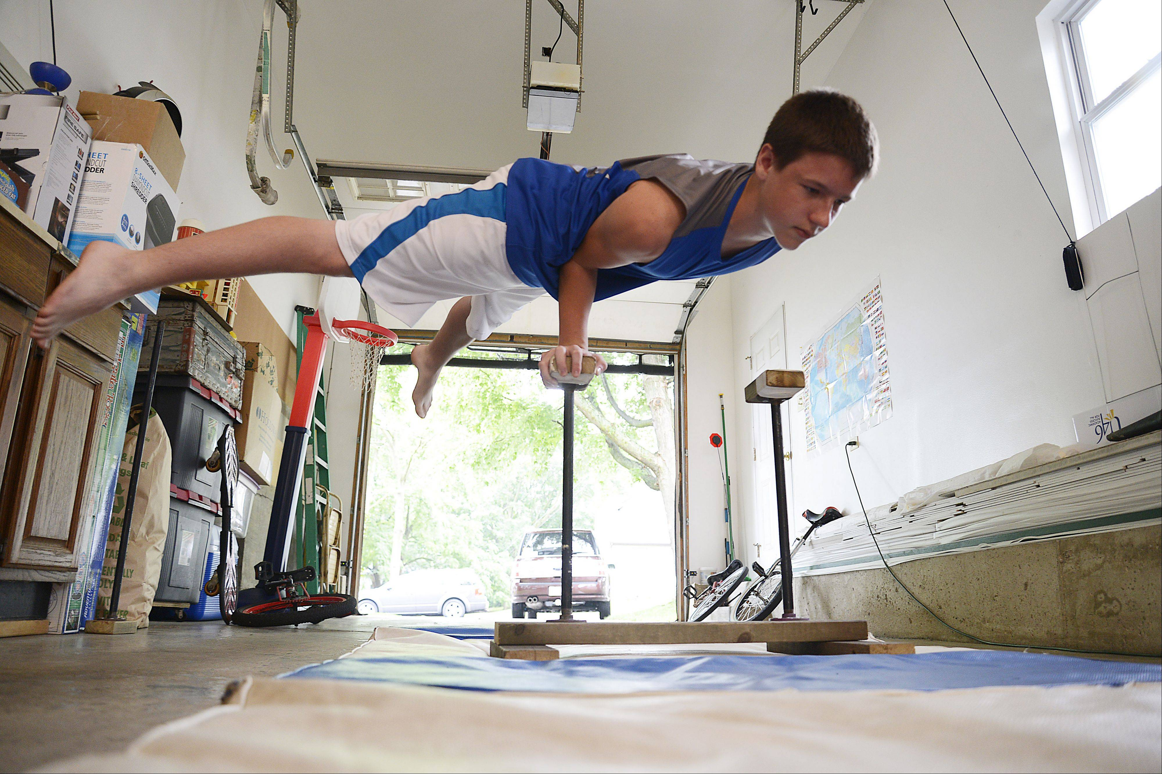 Nick Balk, 14, balances on one hand on 18-inch high balancing canes he made out of leftover lumber and pipes. He prefers strength tricks while sister Katie, 16, prefers balancing and flexibility tricks.