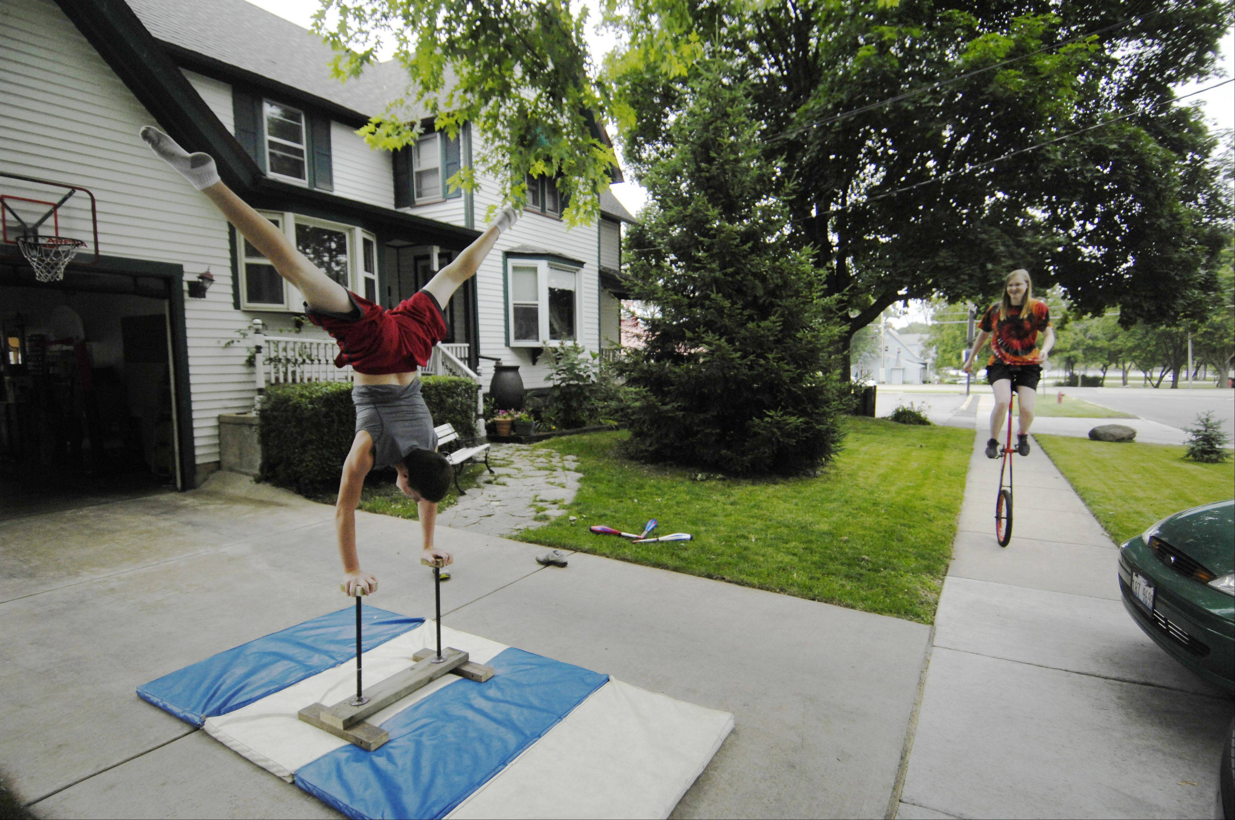 Siblings Katie and Nick Balk use their garage on Prairie Street in South Elgin as their personal circus tent. Nick balances on his homemade balancing canes as Katie, 16, pedals a unicycle in front of their house in South Elgin.