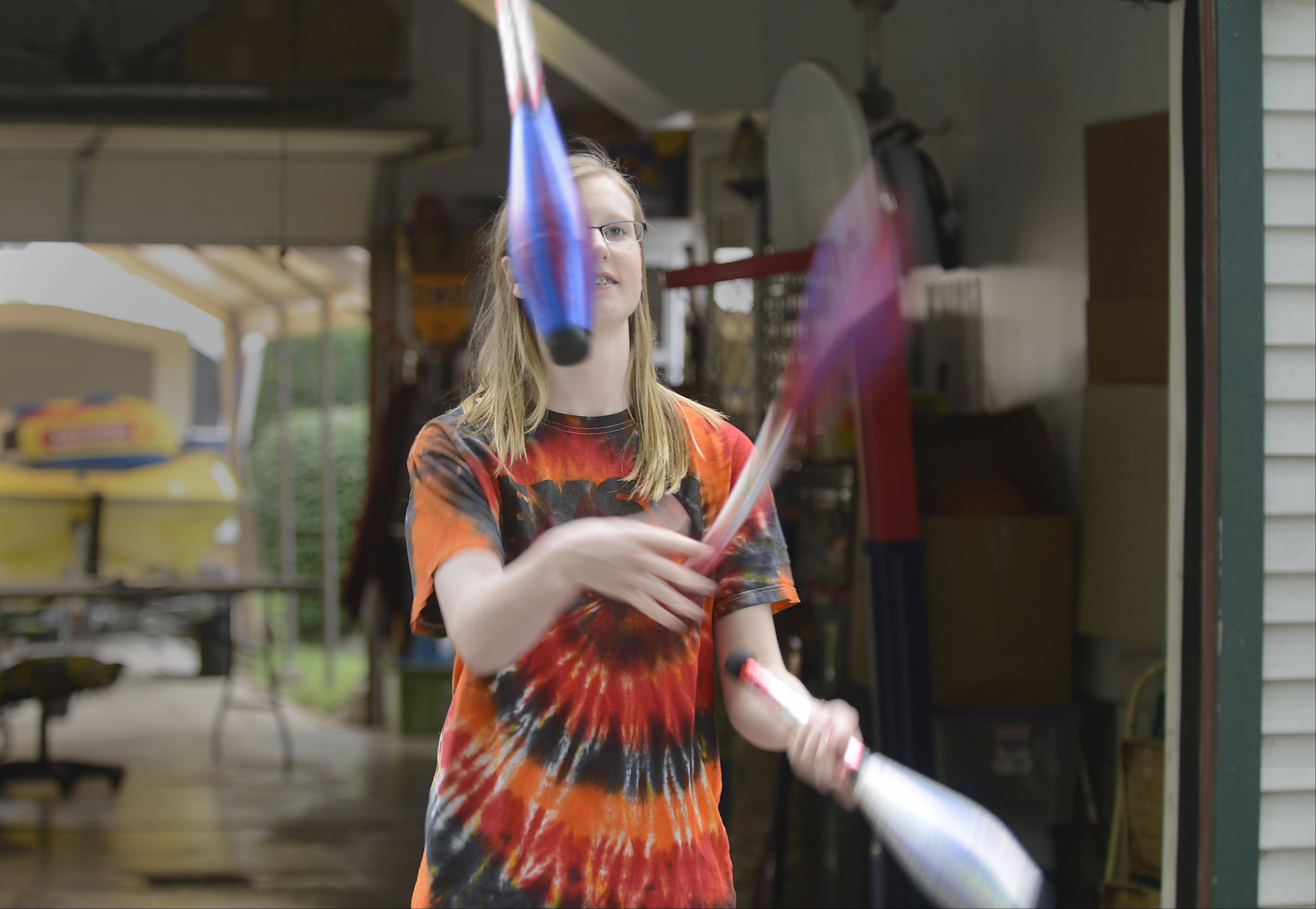 Katie made juggling pins out of pop bottles before getting professional equipment. She can now juggle homemade flaming tiki torches.