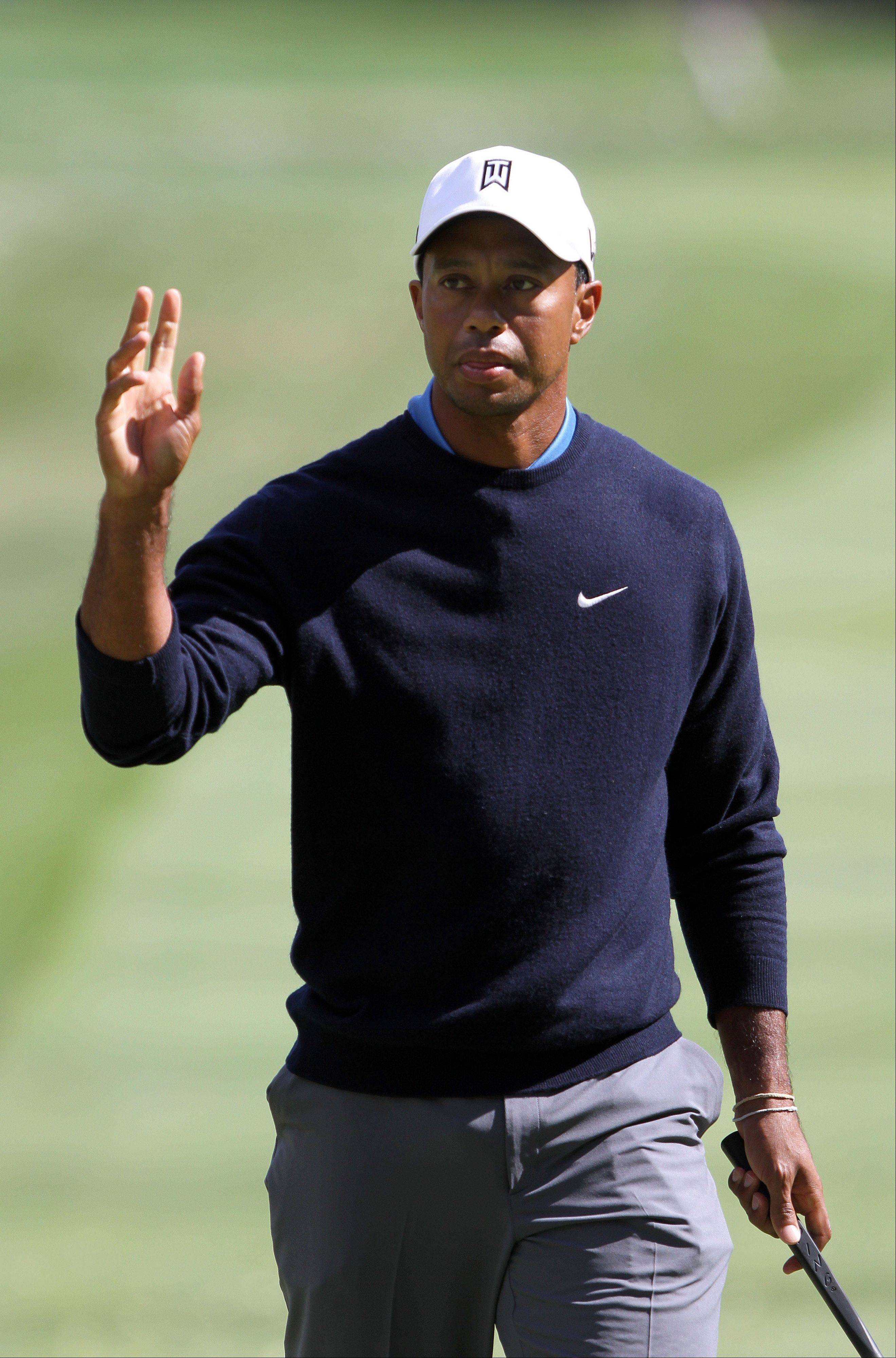 Tiger woods acknowledges the crowd after making a birdie on the 9th hole.