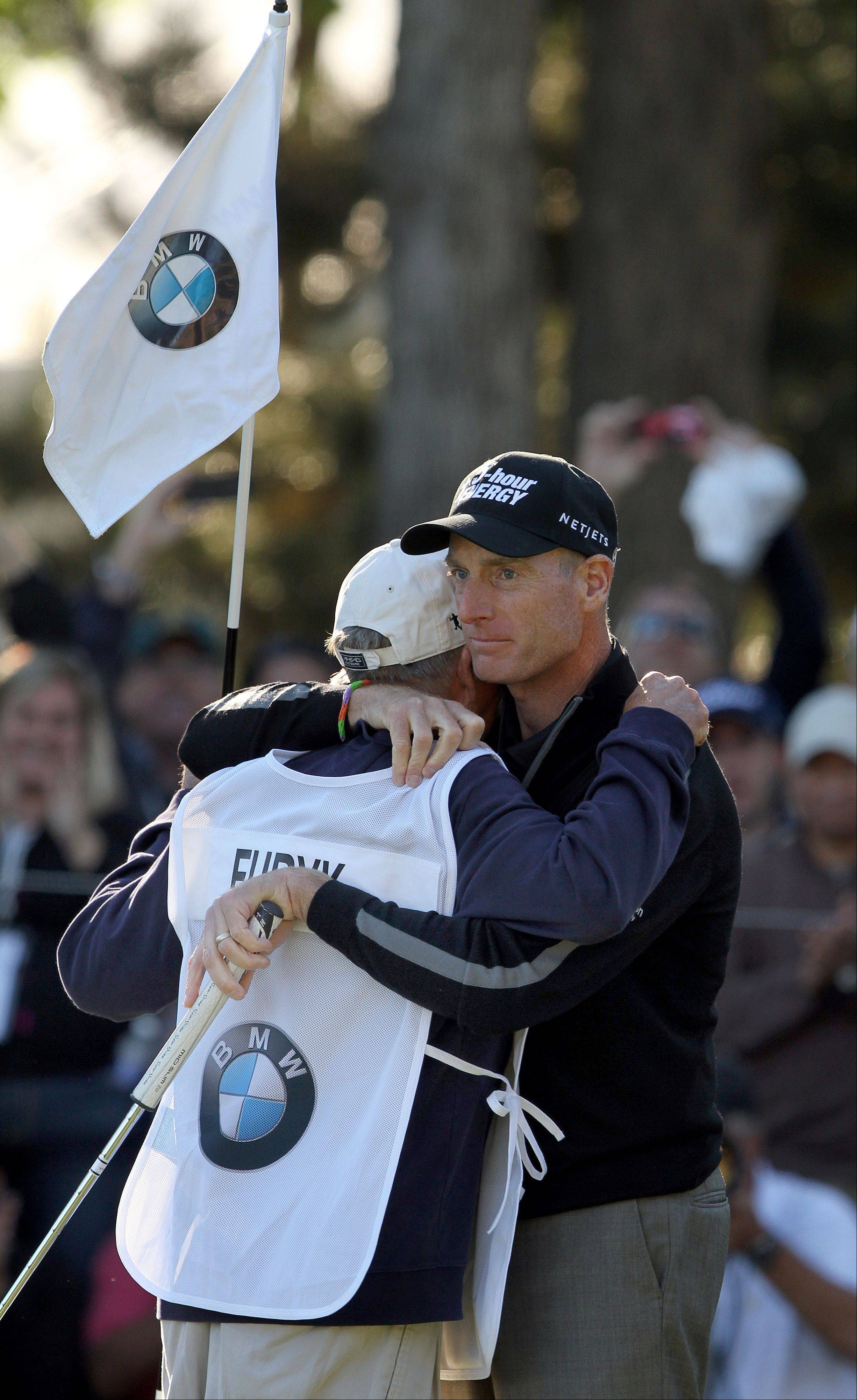 "Jim Furyk hugs his caddy Mike ""Fluff"" Cowan after Friday's round."