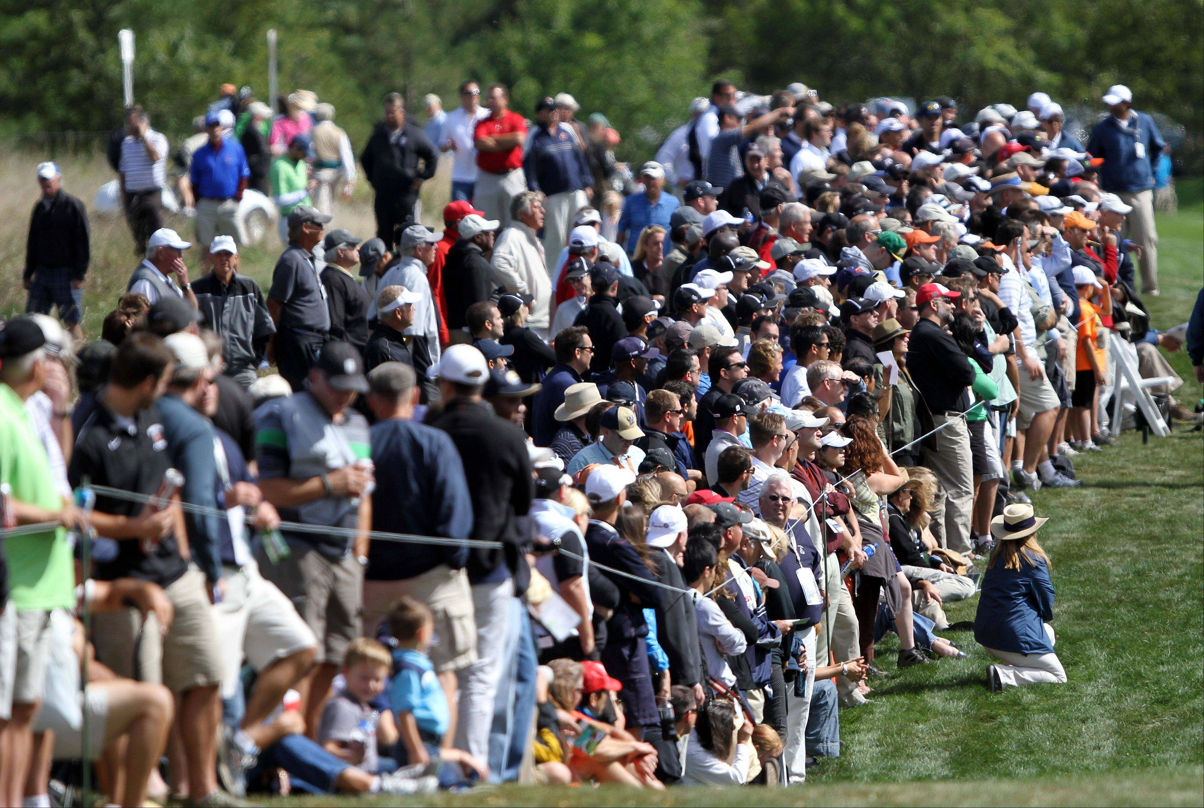 Fans in the gallery line the 9th hole as Jim Furyk approaches.