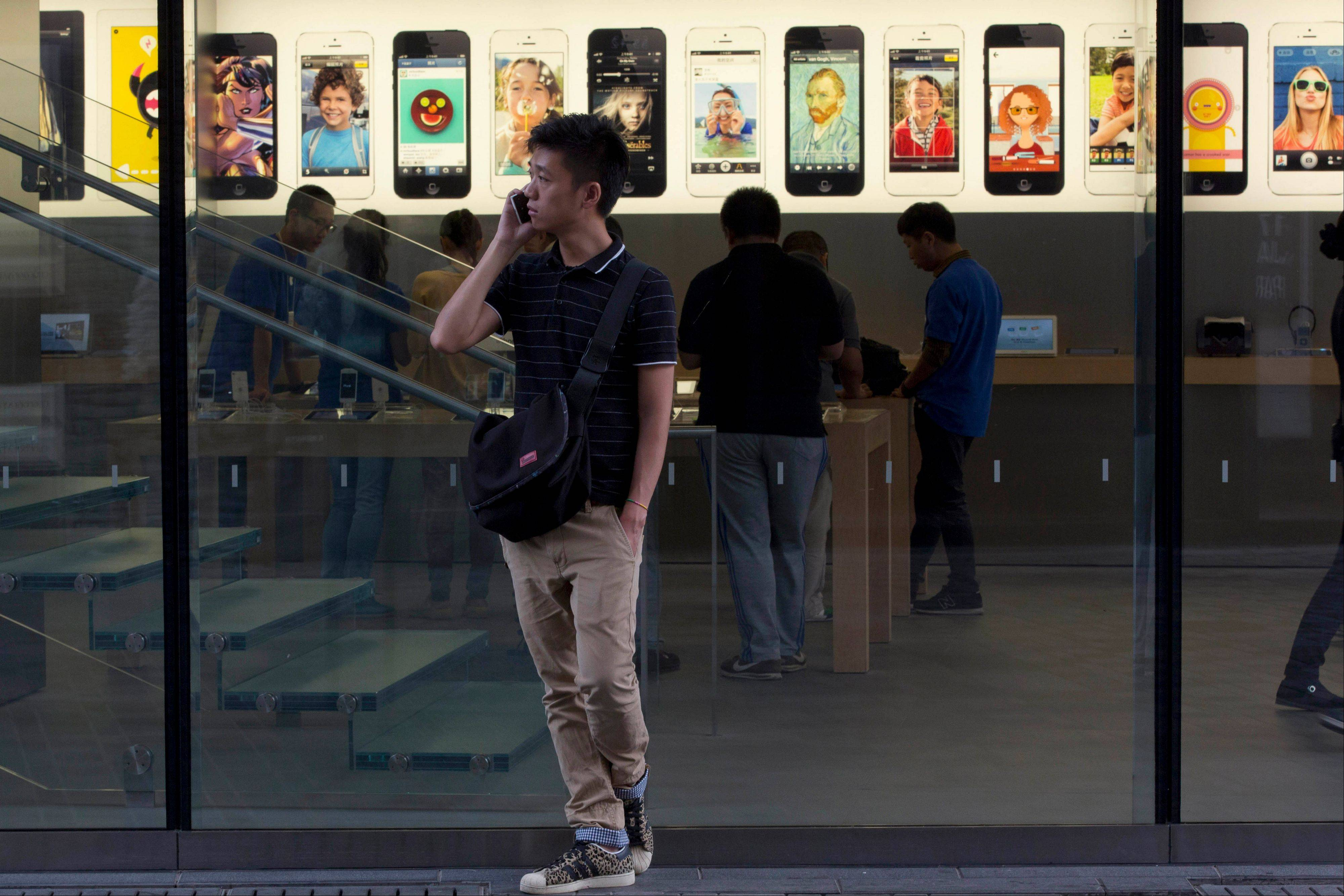 A Chinese man uses a non-Apple branded mobile phone Thursday outside a store with iPhone advertisements in Beijing. Many Chinese gadget lovers responded with a shrug when Apple Inc. unveiled two its new iPhone 5 this week. Today�s market is glutted with alternatives from Samsung to bargain-priced local brands.
