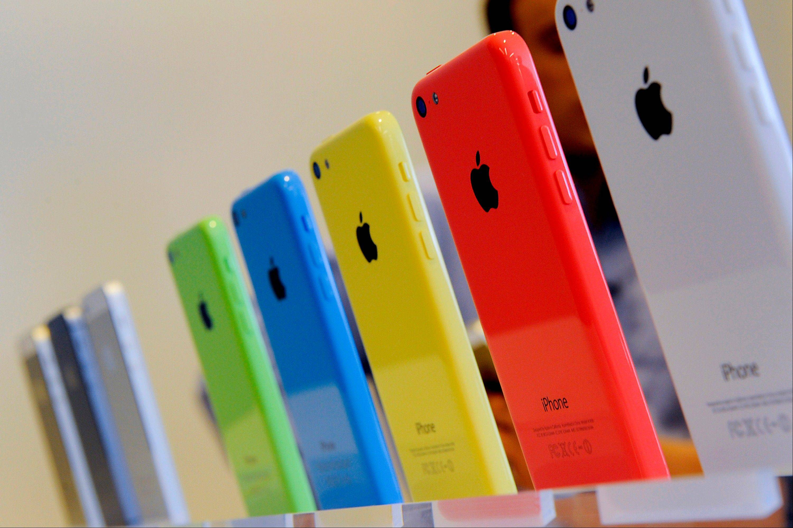 The new Apple Inc. iPhone 5C sit on display Tuesday during a product announcement in Cupertino, California, U.S. Apple Inc. announced two new iPhones including one with lower prices and more color options, in a strategy shift by Cook to reach a broader range of customers around the world.