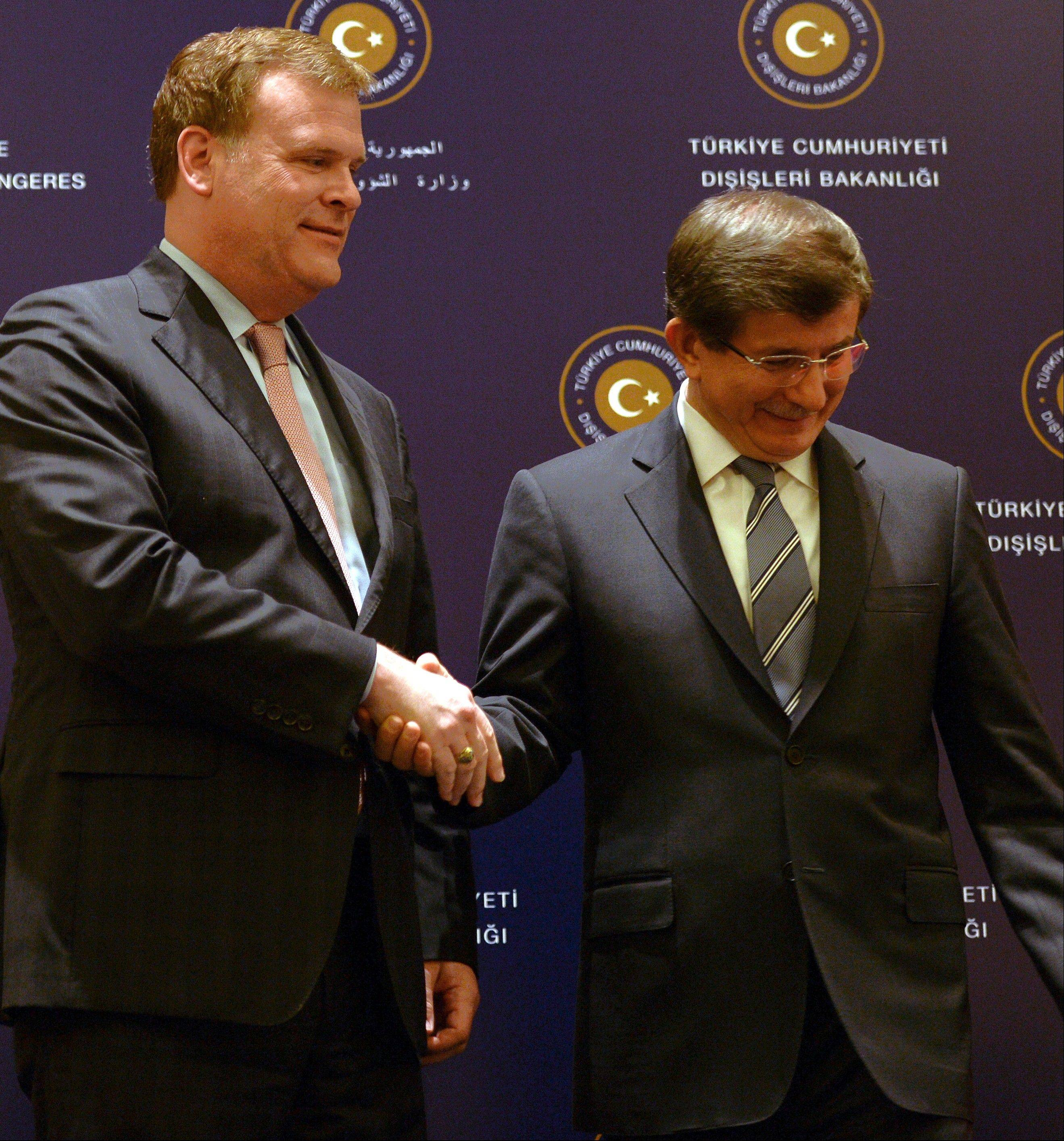 Canadian Foreign Minister John Baird, left, and his Turkish counterpart Ahmet Davutoglu shake hands Saturday in front of the media during a news conference after talks on security and terror threats in the mideast region, in Istanbul, Turkey.