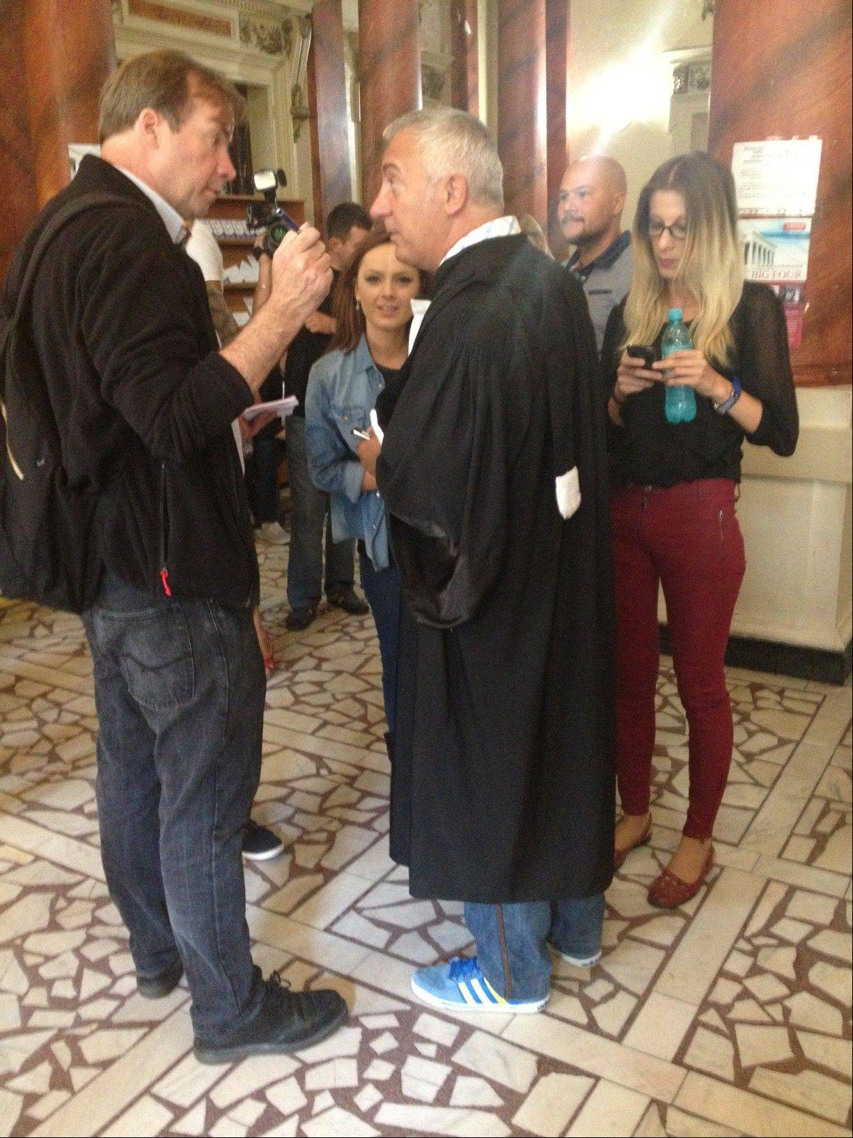 Media surround lawyer Catalin Dancu who stands in a court in Bucharest wearing his sneakers Tuesday Sept 10 2013. A judge fined Dancu 5,000 lei ($1482 ) Tuesday for flouting dress regulations and for arriving late at the trial of four Romanians who are being tried over the theft of seven paintings, causing the case to be suspended. Dancu says he has apologized for being late, due to another case, but would contest the sneaker ruling.