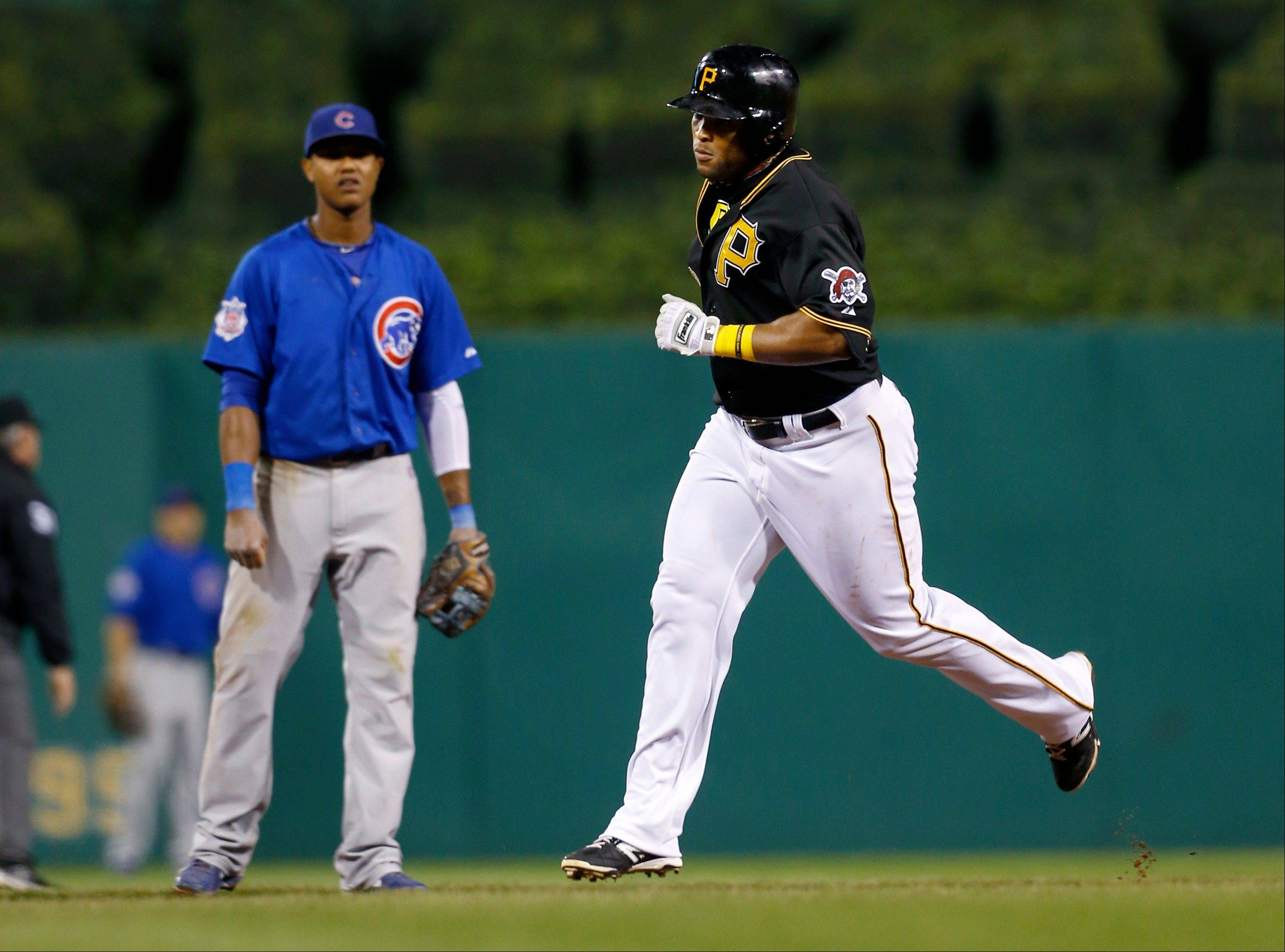 Pittsburgh Pirates� Marlon Byrd, right, rounds the bases in front of Chicago Cubs� Darwin Barney after hitting a home run in the seventh inning of the baseball game on Saturday, Sept. 14, 2013, in Pittsburgh. The Pirates won 2-1.