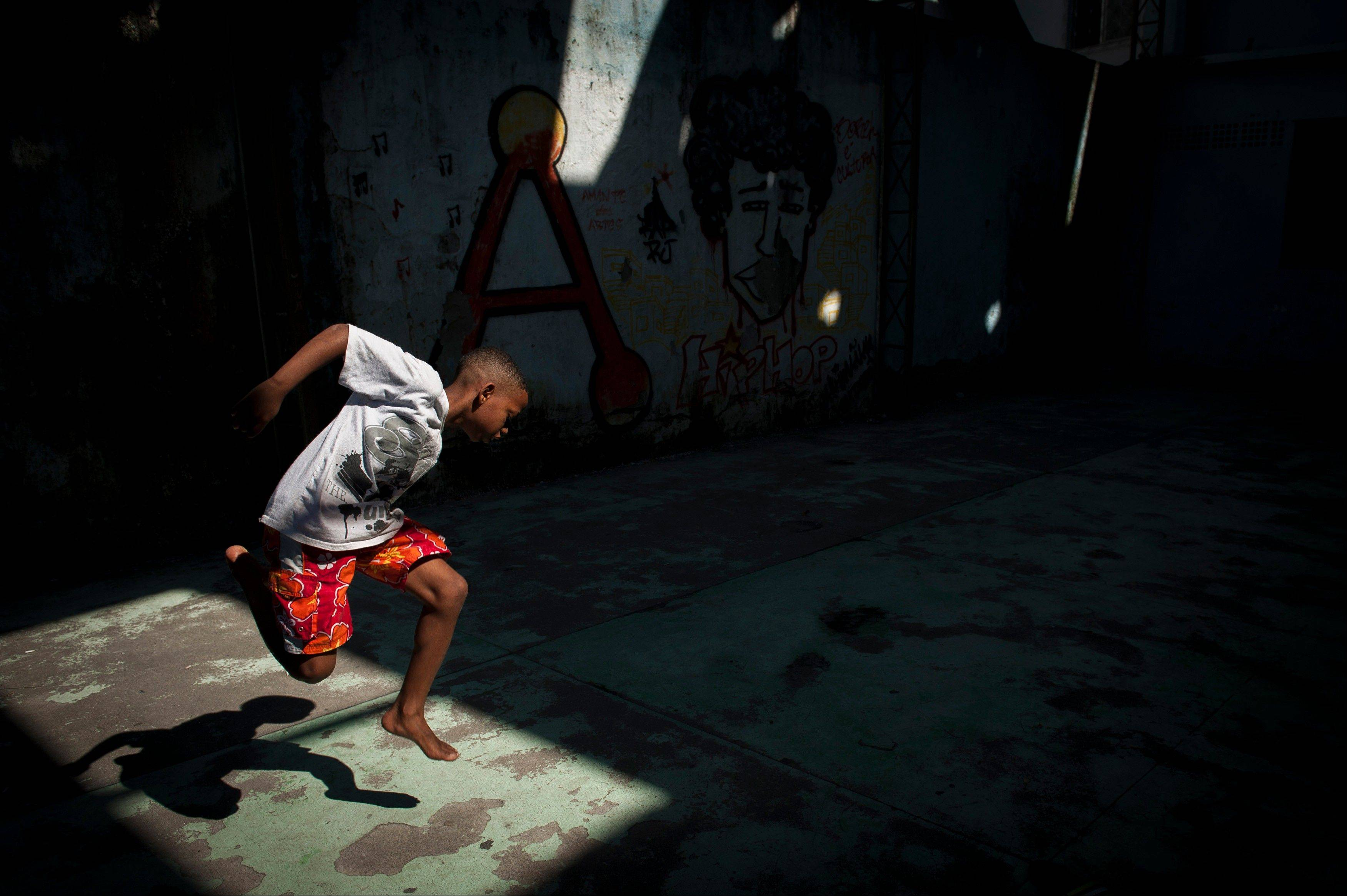 "A boy jumps in the air and grabs his foot while practicing a step from a dance form called ""passinho,"" or ""little step."""
