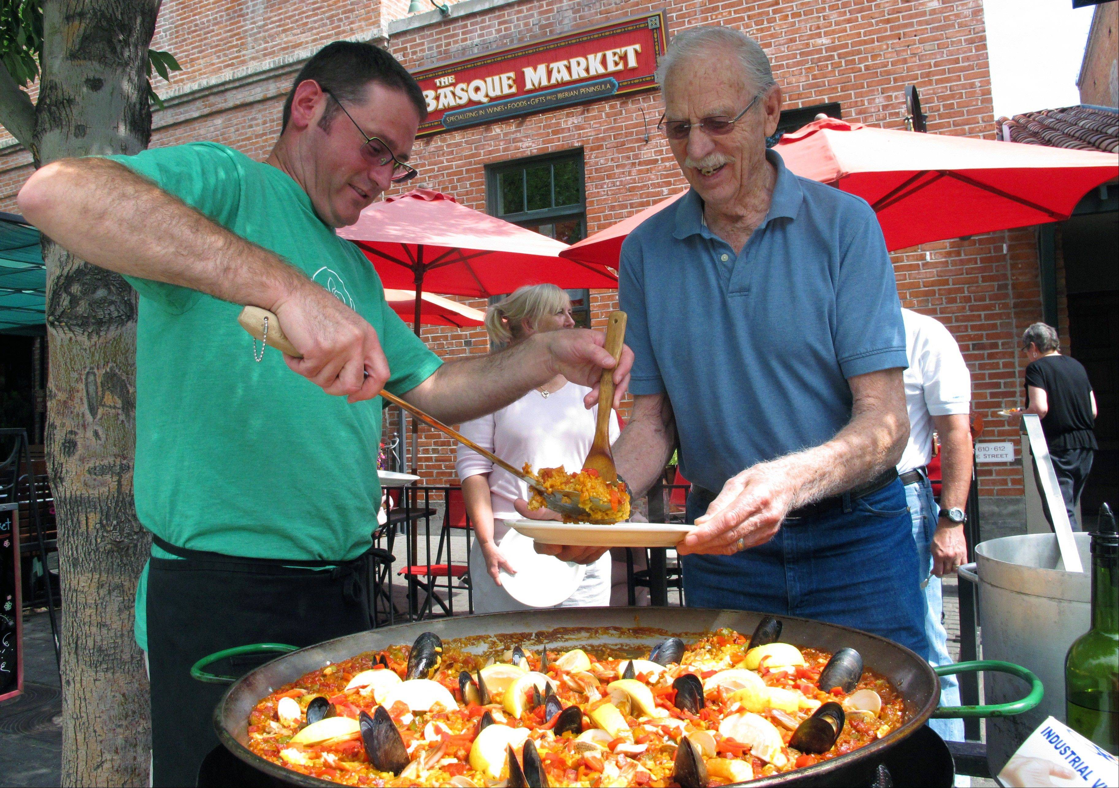 Tony Eiguren, left, owner of the Basque Market, serves a plate of paella to a lunch customer in Boise, Idaho.