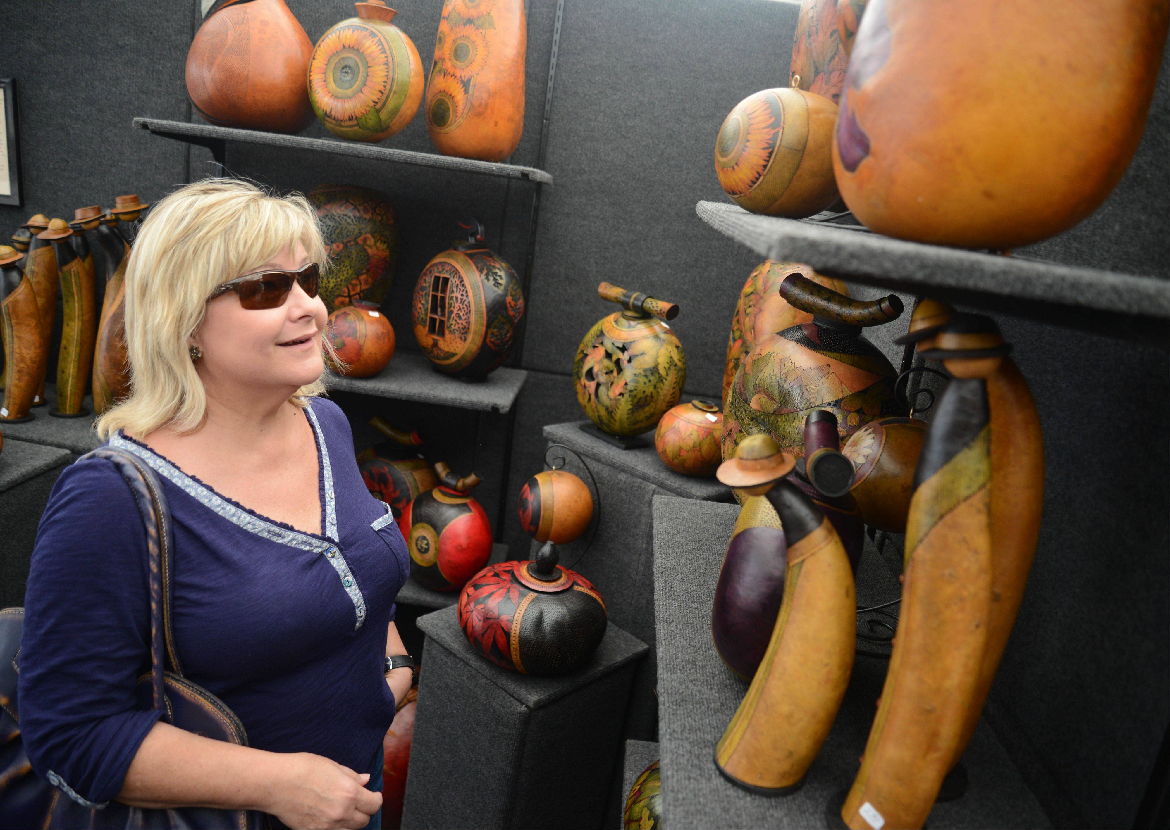 Linda Thoma of Naperville looks at gourd art by Beth and Steve Radtke of Georgia on Saturday during the Naperville Art League's annual Riverwalk Fine Art Fair in Naperville.