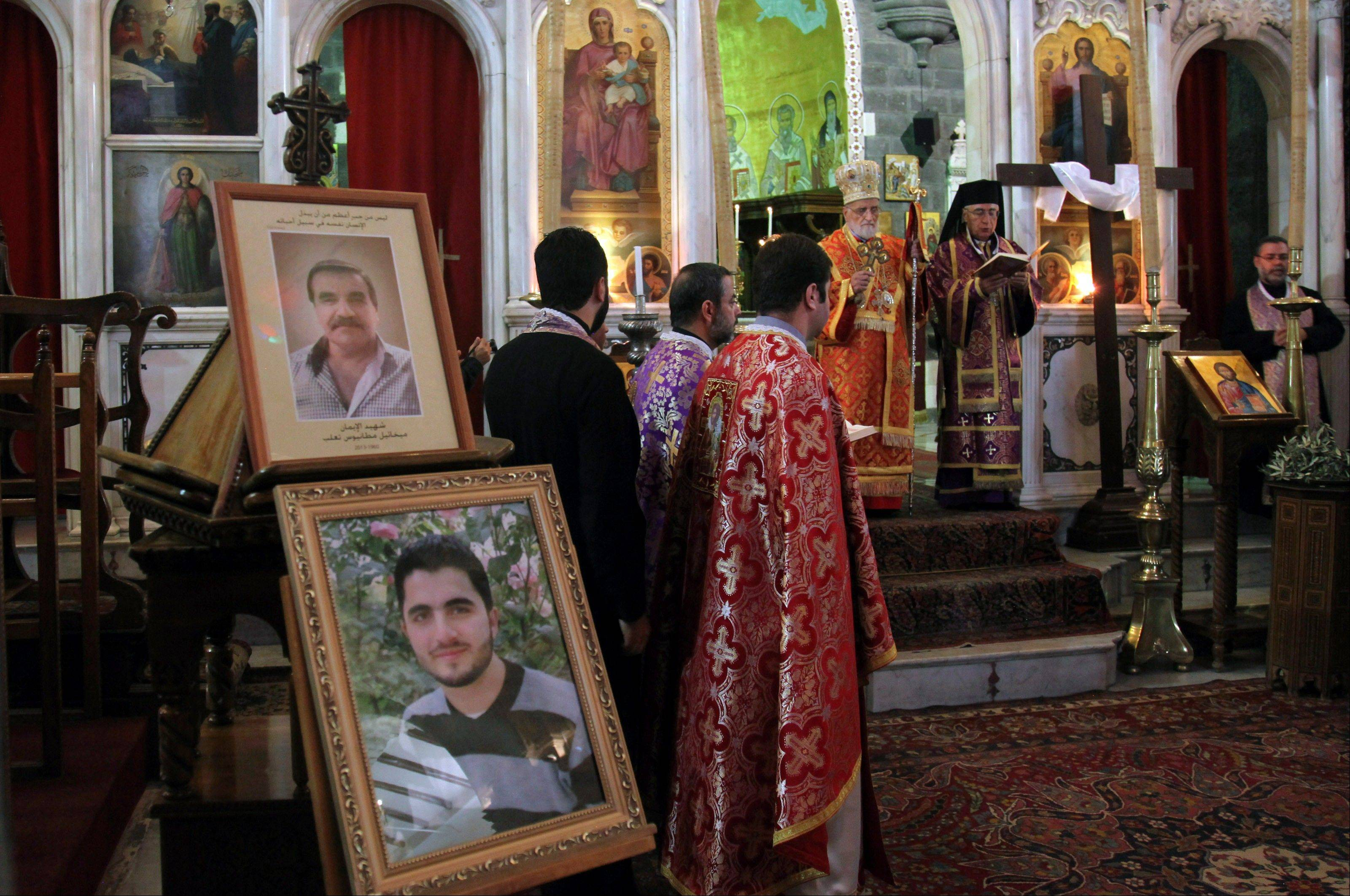 Portraits of two men are on display as people pray Saturday for three Christian men killed by gunmen in the predominately Christian village of Maaloula during a service at the al-Zaytoun Roman Catholic Church, Damascus, Syria.