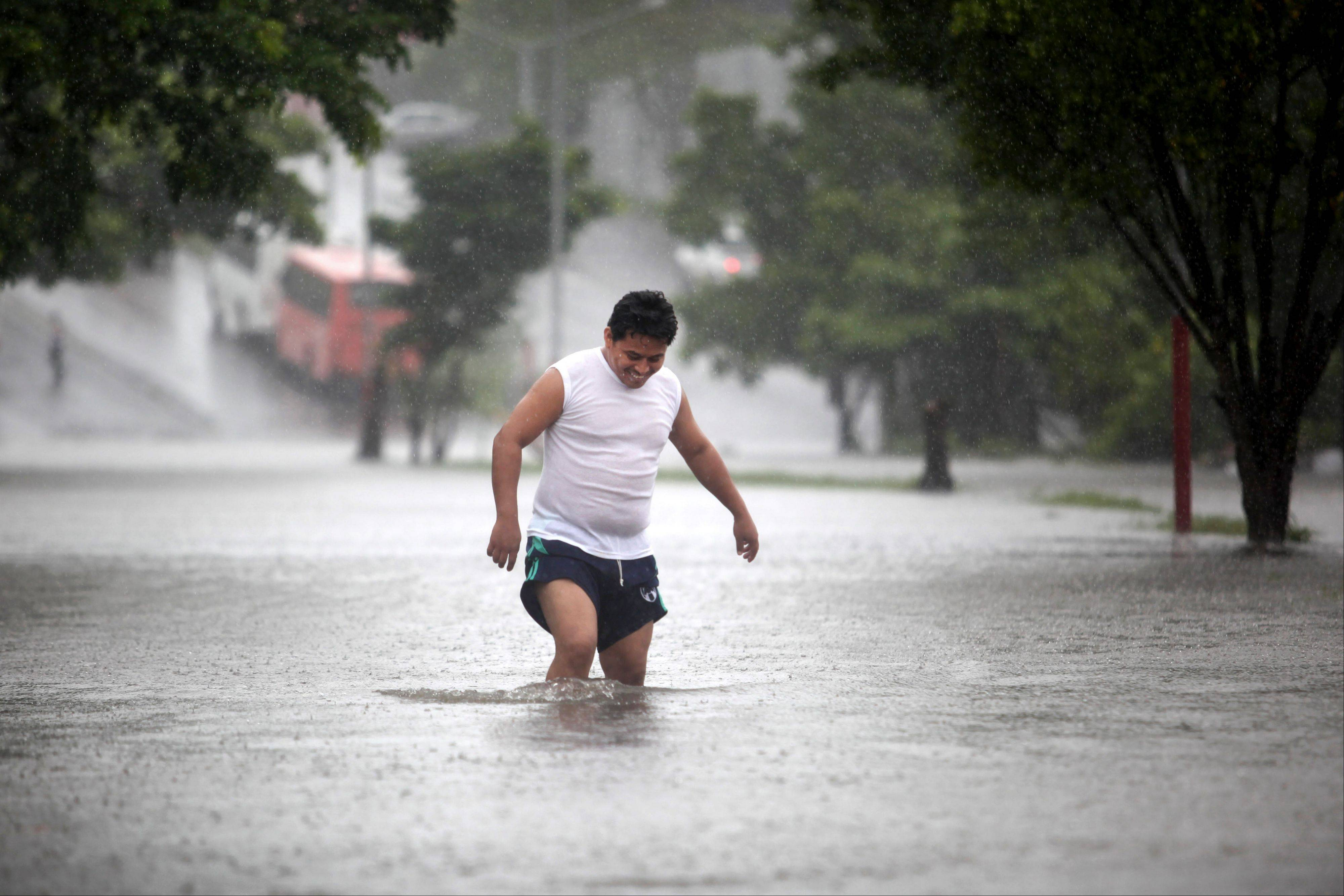 A man walks through a flooded street Friday during heavy rains caused by Tropical Storm Ingrid in the Gulf port city of Veracruz, Mexico.