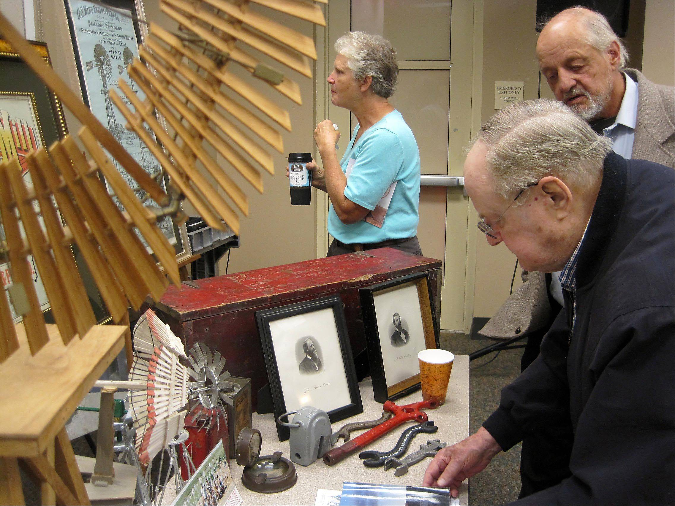 Hugh Cole of Wilmette, foreground, looks at a display of historic windmill artifacts on Saturday at the Batavia Public Library. Next to him is Dick Riseling, a Batavia native who now lives in New York. Both men attended a ceremony that designated Batavia's windmill collection as an engineering landmark by the American Society of Mechanical Engineers.