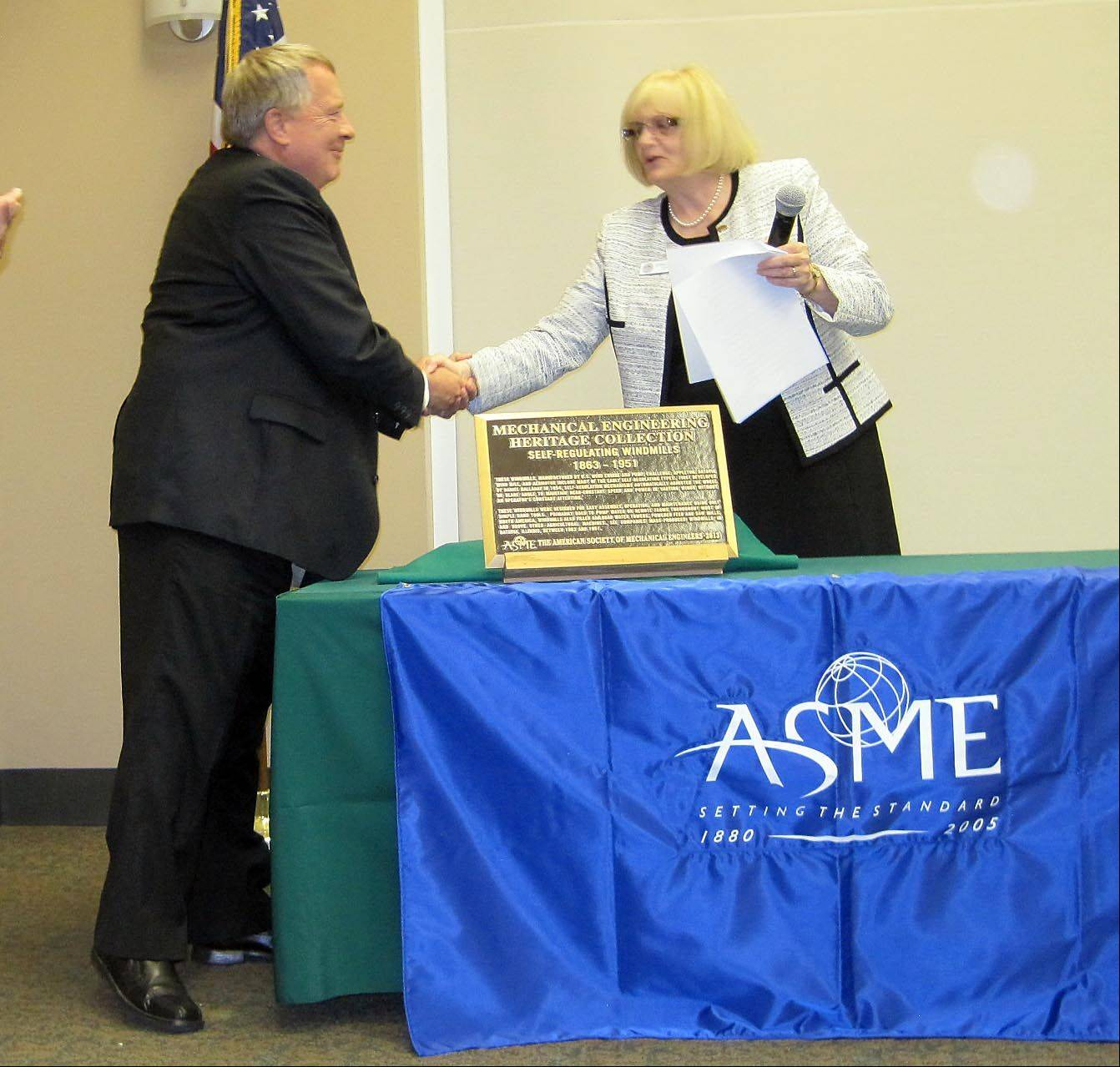 Batavia Mayor Jeff Schielke, left, and Victoria Rockwell, past president of the American Society of Mechanical Engineers, shake hands after the unveiling of a commemorative plaque designating Batavia's windmills as an engineering landmark in a ceremony held Saturday at the Batavia Public Library.