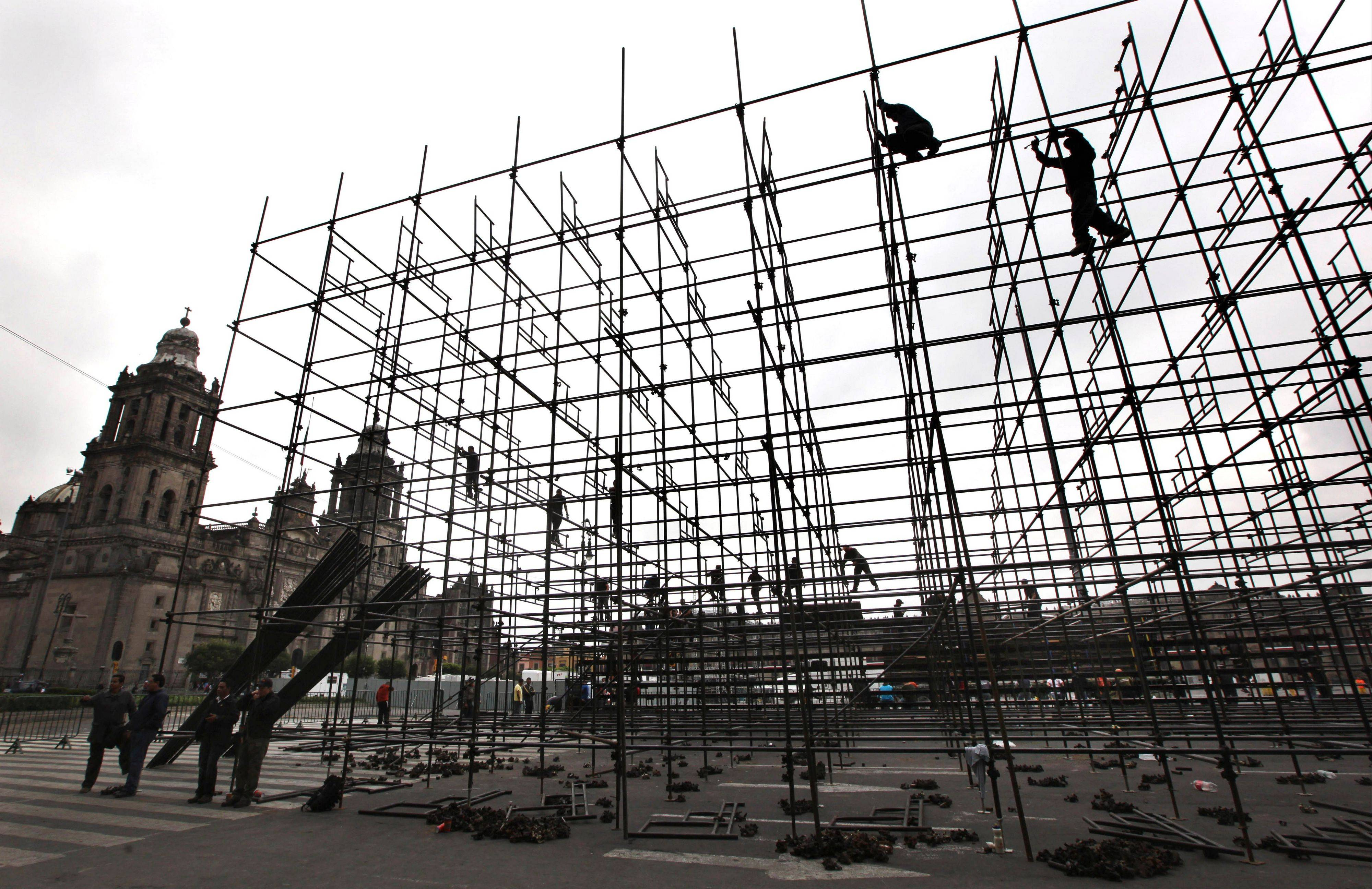 Workers build structures to be used for upcoming Independence Day celebrations in the Zocalo, where striking teachers were kicked out the previous day in Mexico City.