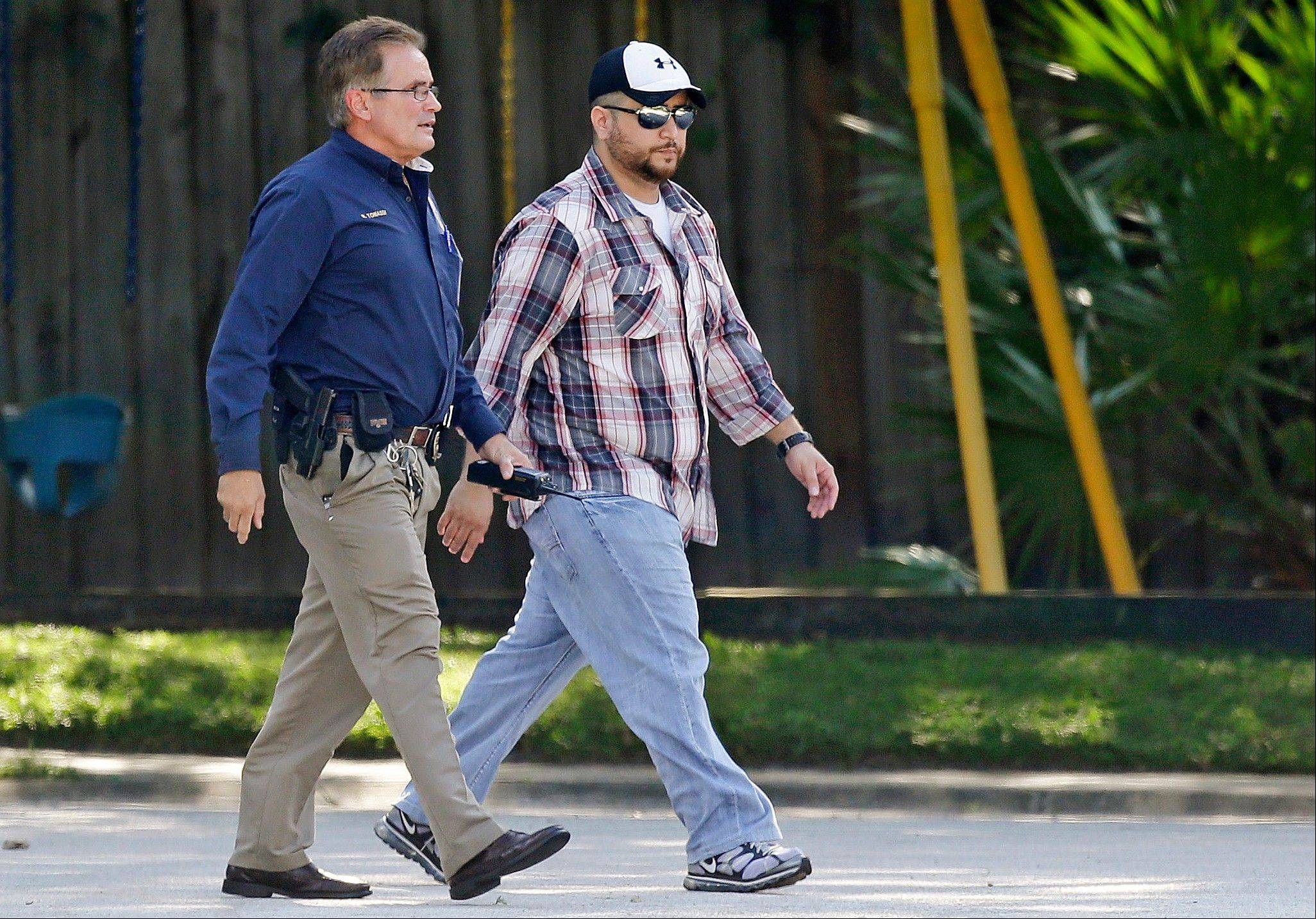 Zimmerman, right, is escorted to a home by a Lake Mary police officer, in Lake Mary, Fla., after a domestic incident in the neighborhood where Zimmerman and his wife Shellie had lived during his murder trial.